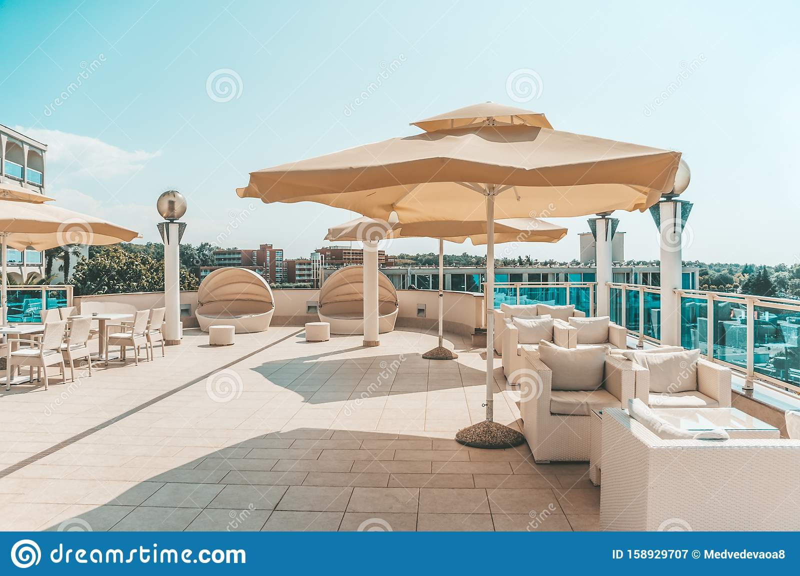 Large White Umbrella And Outdoor Furniture Sofas And Rattan Chairs With Cushions And A Glass Topped Table Place To Relax On The Stock Image Image Of Furniture House 158929707