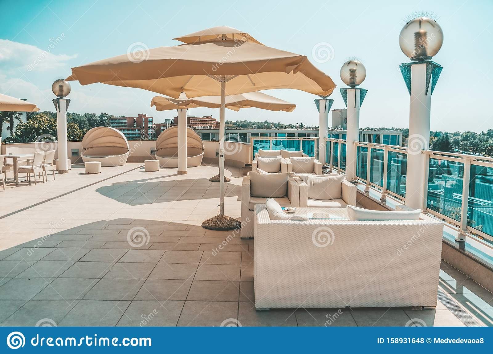 Large White Umbrella And Outdoor Furniture Sofas And Rattan Chairs With Cushions And A Glass Topped Table Place To Relax On The Stock Photo Image Of Furniture Cushions 158931648