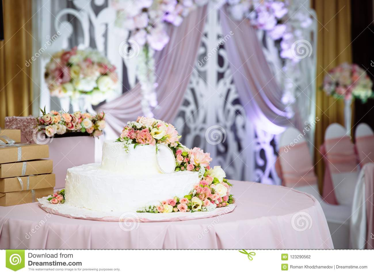 A Large White Wedding Cake On The Table Decorated With Fresh