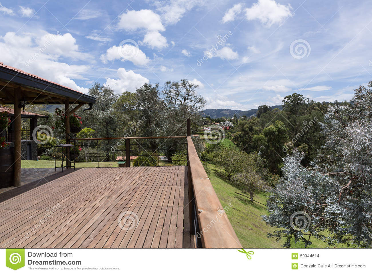 Large wood deck near house with spring landscape.