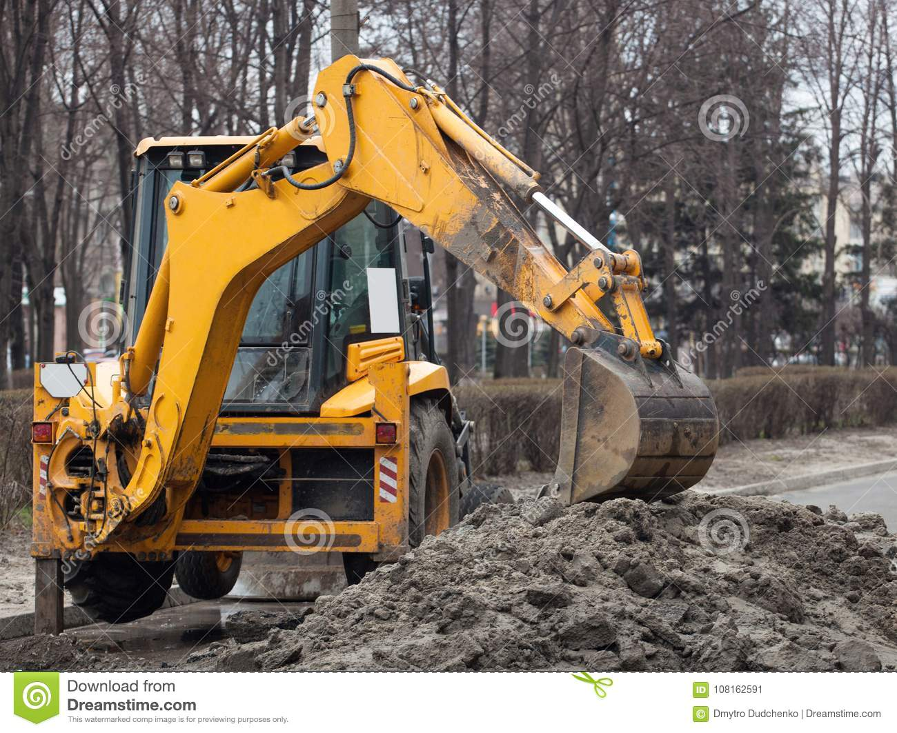 A large yellow excavator stands in the middle of the street near the dug hole
