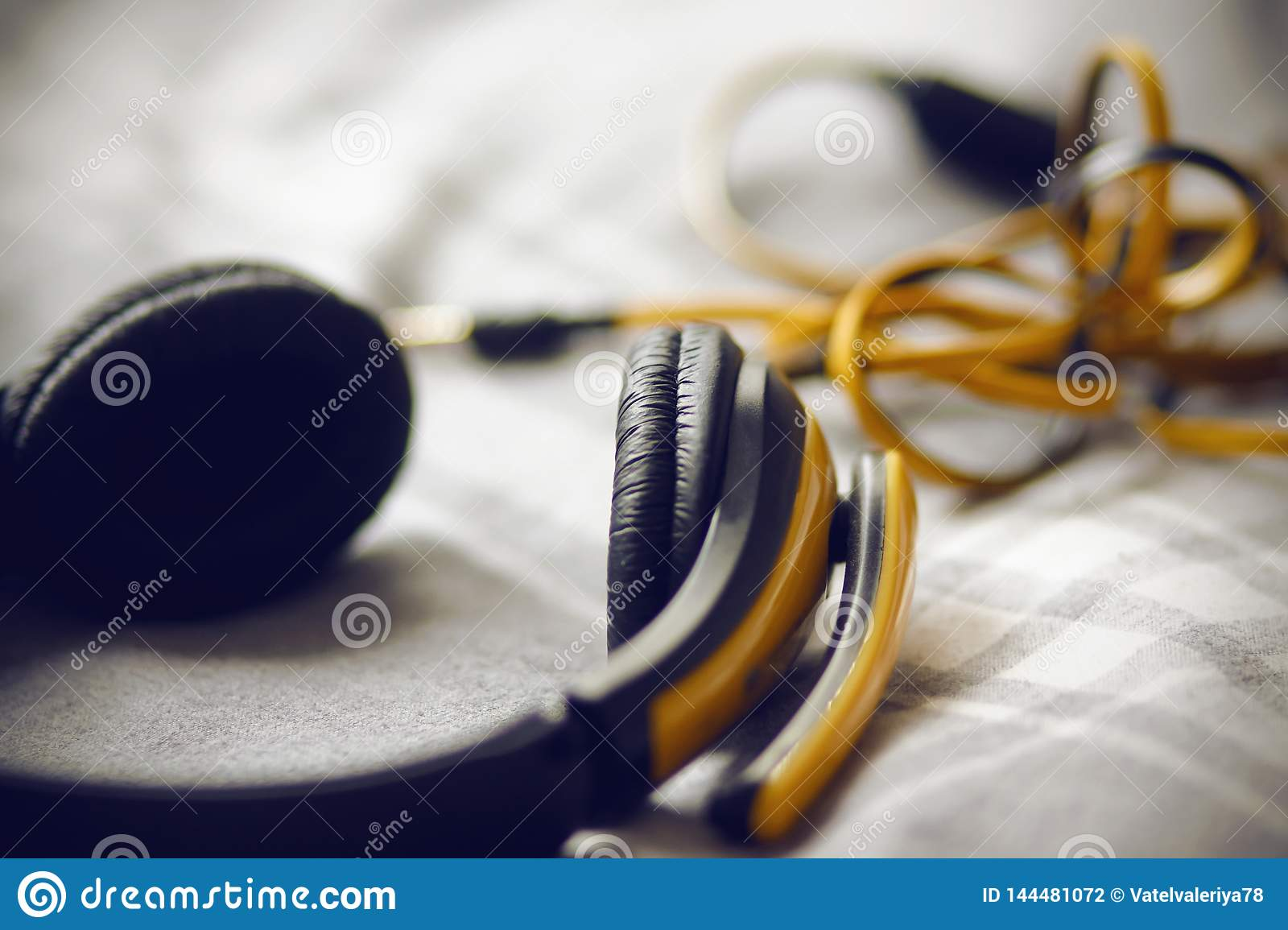 Large yellow headphones lie on a gray plaid