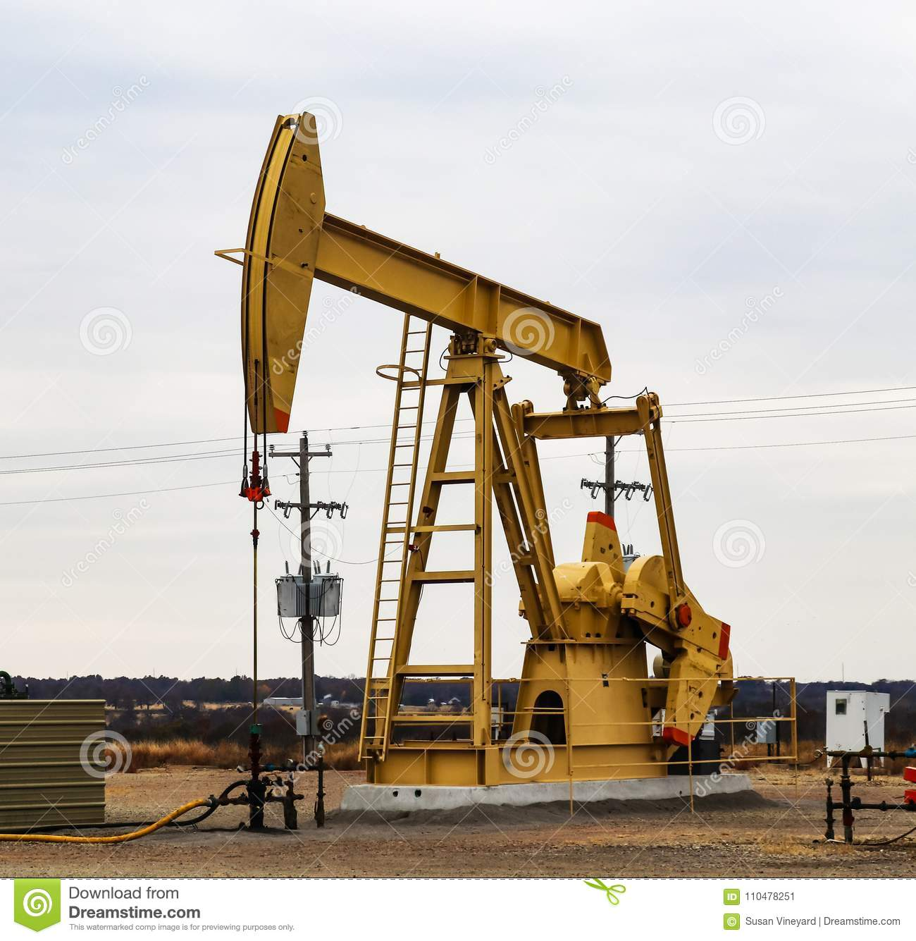 Large Yellow 912 Pump Jack on oil or gas well with surrounding equipment against an overcast sky
