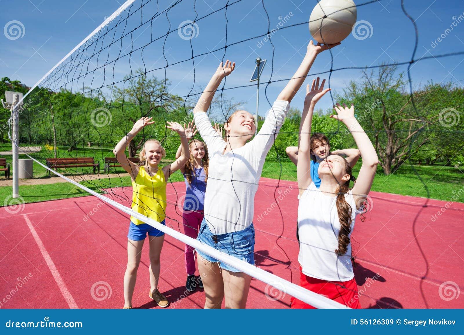 Las adolescencias en el movimiento con los brazos suben voleibol del juego