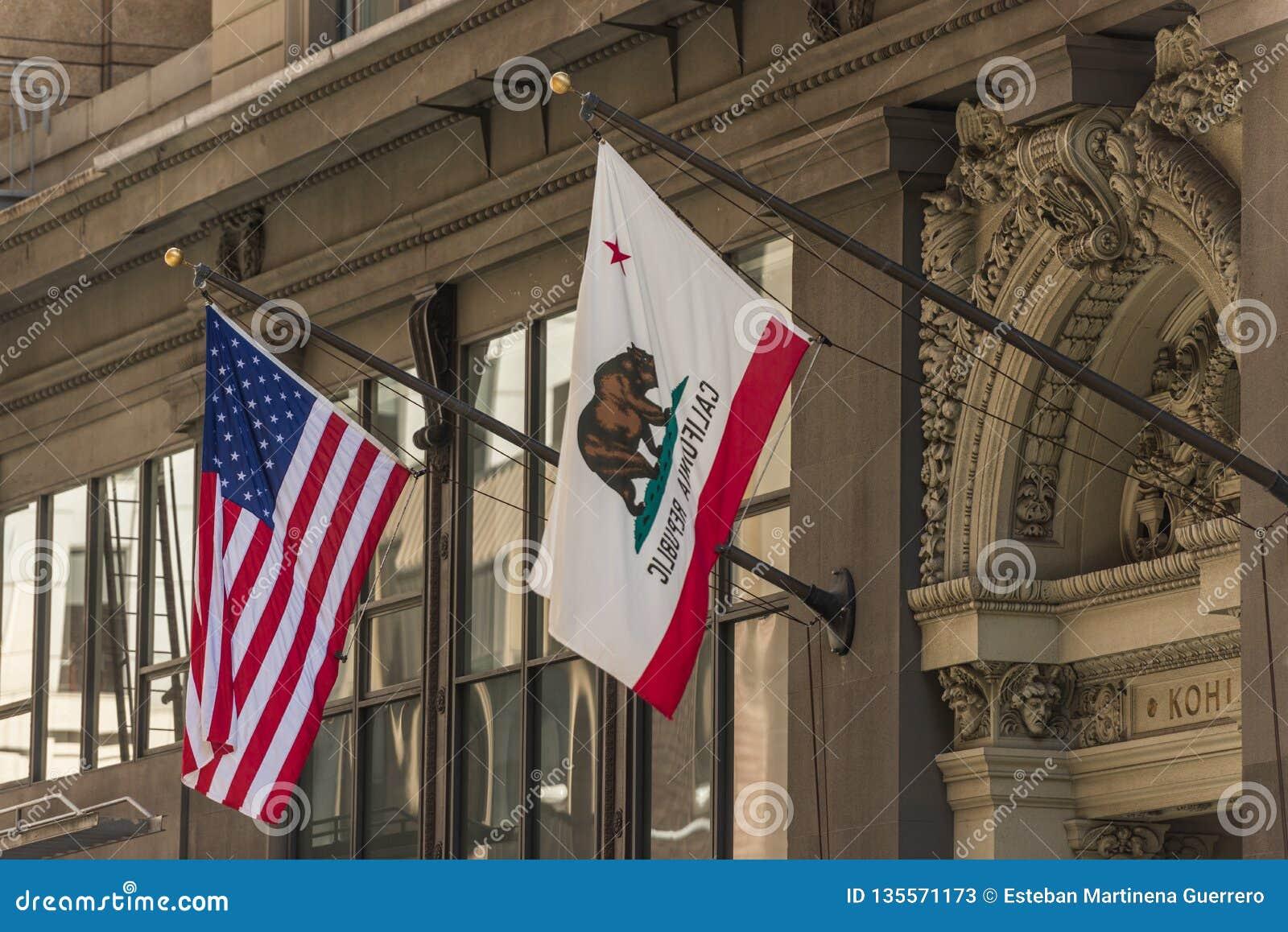 Las banderas de los Estados Unidos y de la California en un edificio en el distrito financiero de San Francisco, California, los