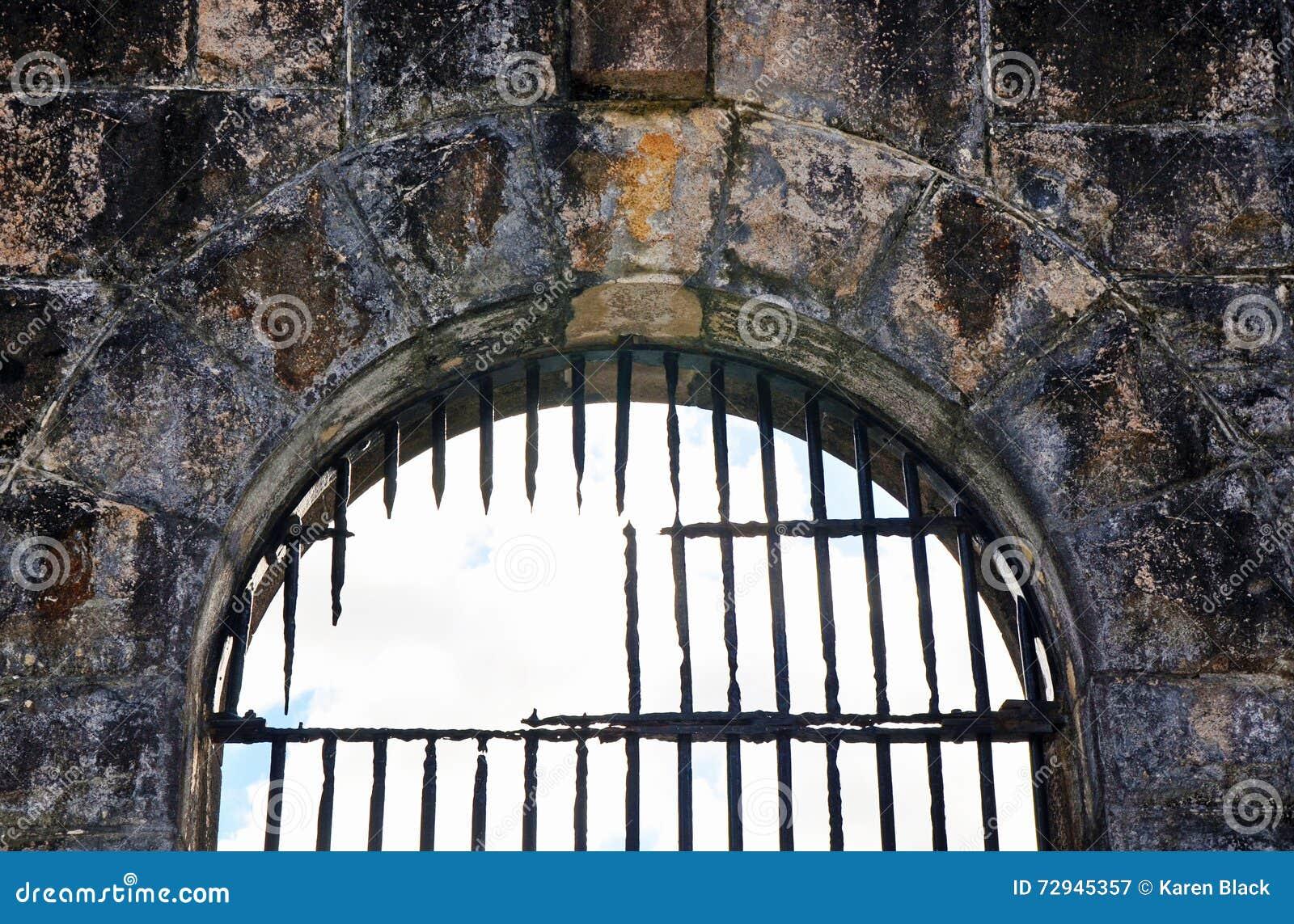 Las barras de hierro oxidadas quebradas en la cárcel vieja (cárcel) arquearon la ventana