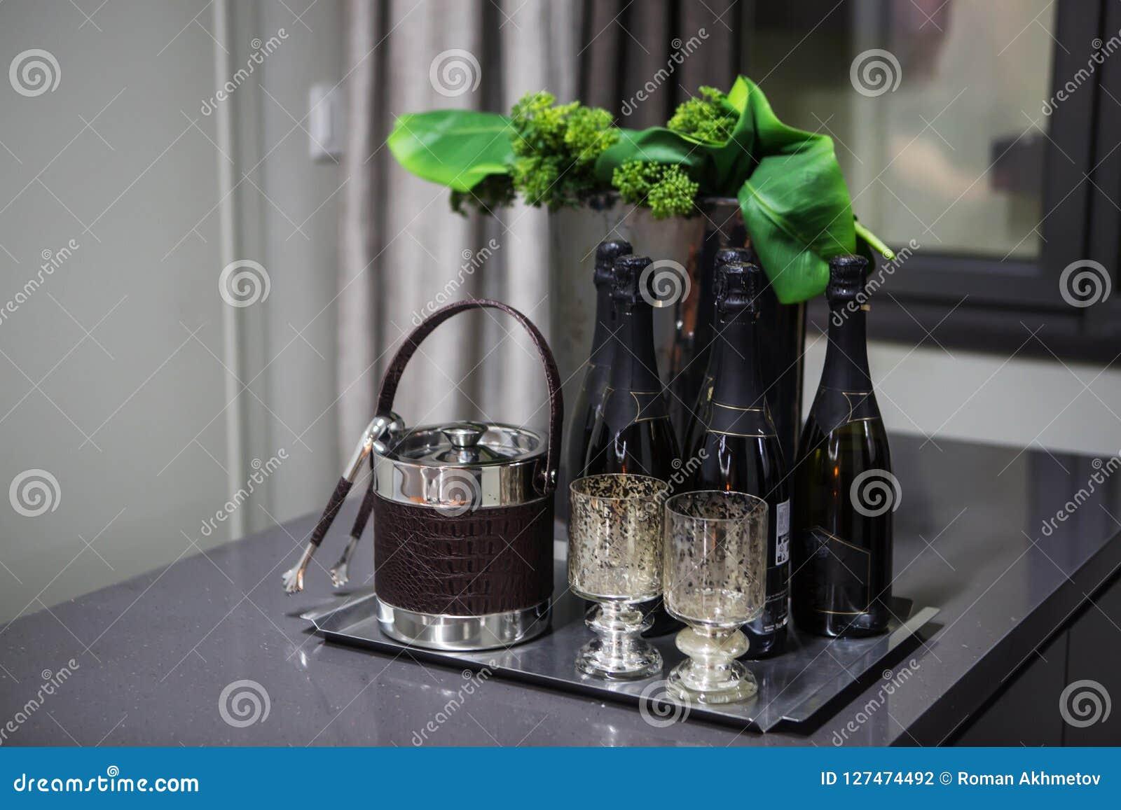 Las botellas negras de champán se colocan en una tabla al lado de los platos para el hielo y las pinzas en el fondo