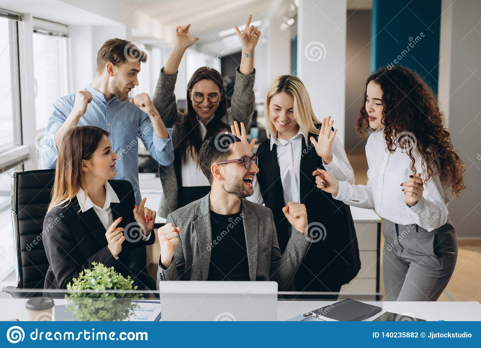 Las buenas noticias de la parte masculina del trabajador con los colegas multirraciales en lugar de trabajo compartido, los emple