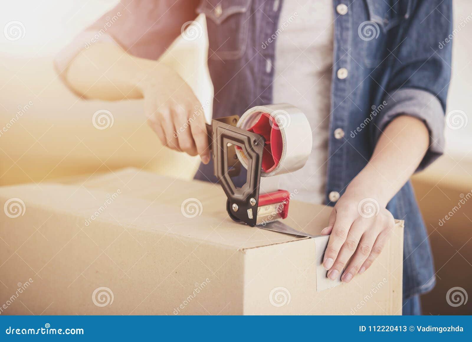 Las cajas de embalaje de la mujer feliz joven Mudanza, compra de la nueva habitación