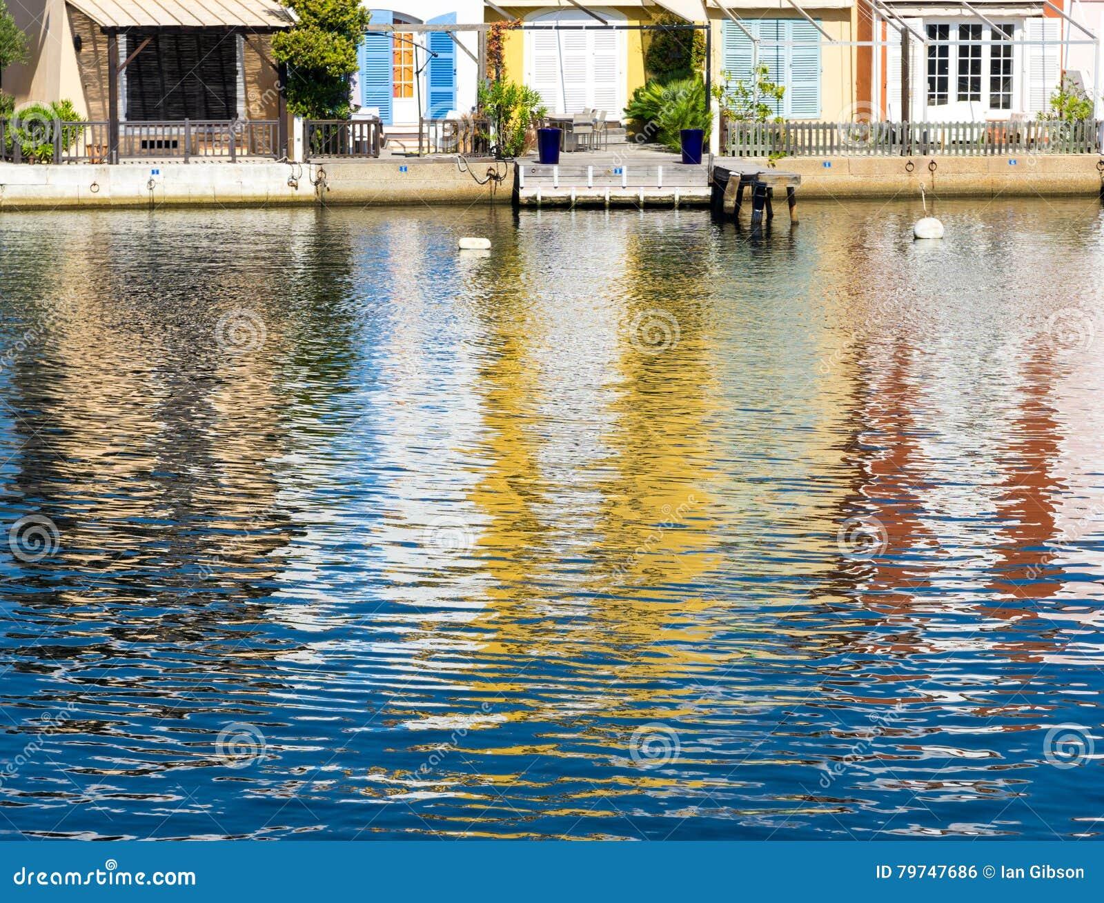 Las casas reflejaron en el agua del puerto Grimaud
