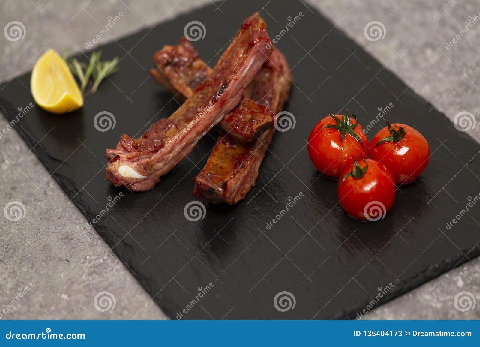 Las costillas de cerdo en salsa y miel de barbacoa asaron los tomates en un plato negro de la pizarra