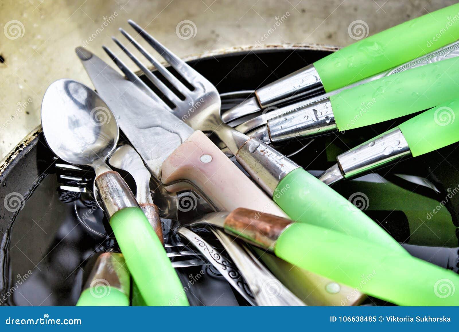 Las cucharas, las bifurcaciones y los cuchillos sucios están en la cacerola vieja en el fregadero af