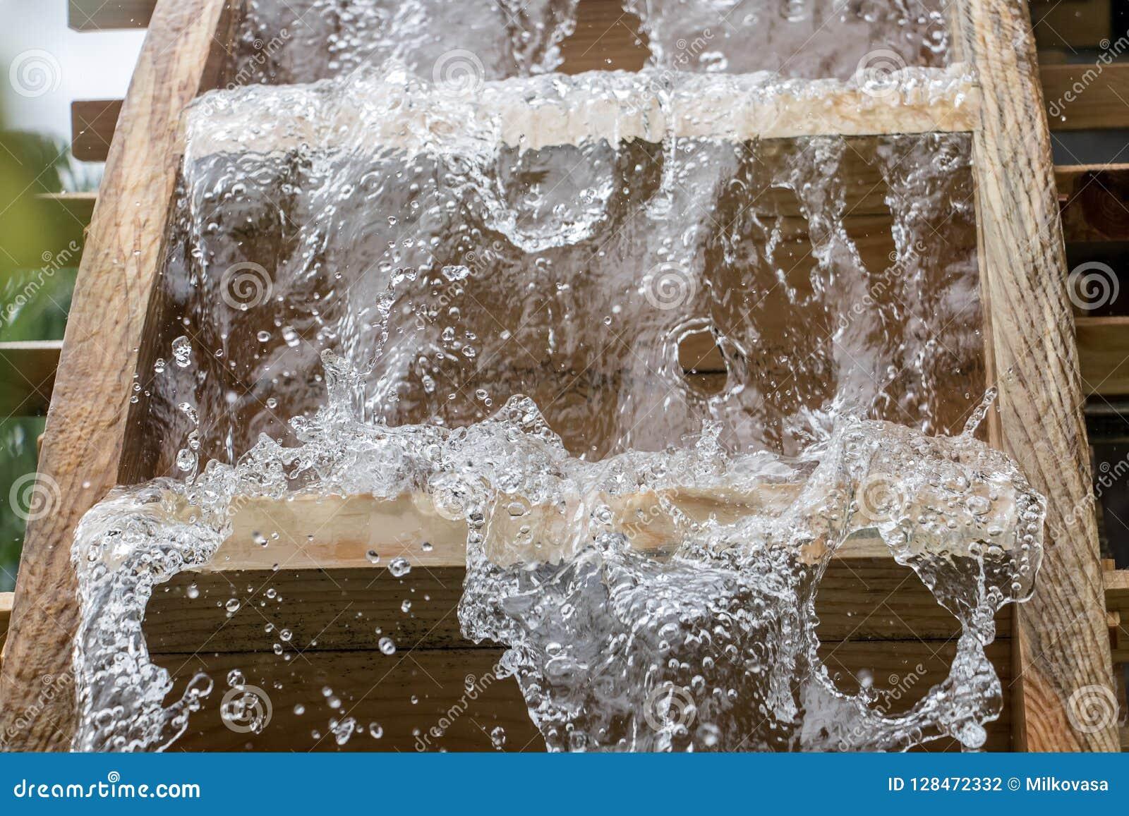 Las cuchillas de la rueda de molino giran debajo de una corriente del agua,