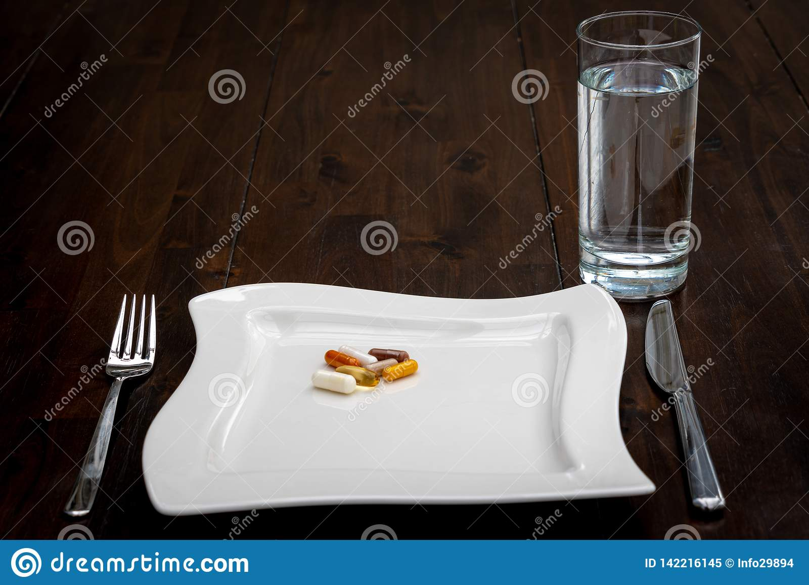 Las diversas píldoras están en las placas blancas al lado de un vaso de agua en una tabla marrón