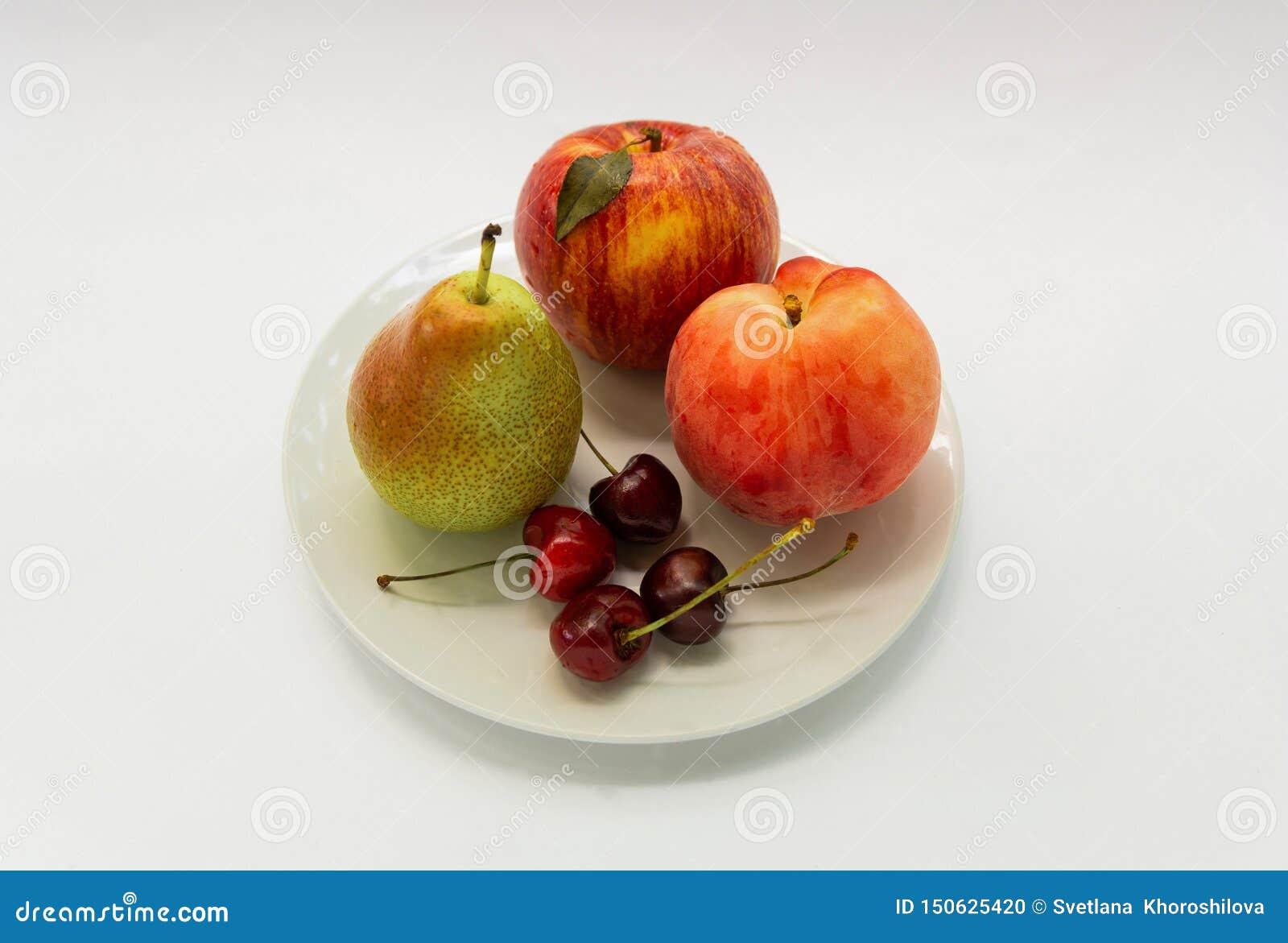 Las frutas frescas mienten en una placa blanca en un fondo blanco
