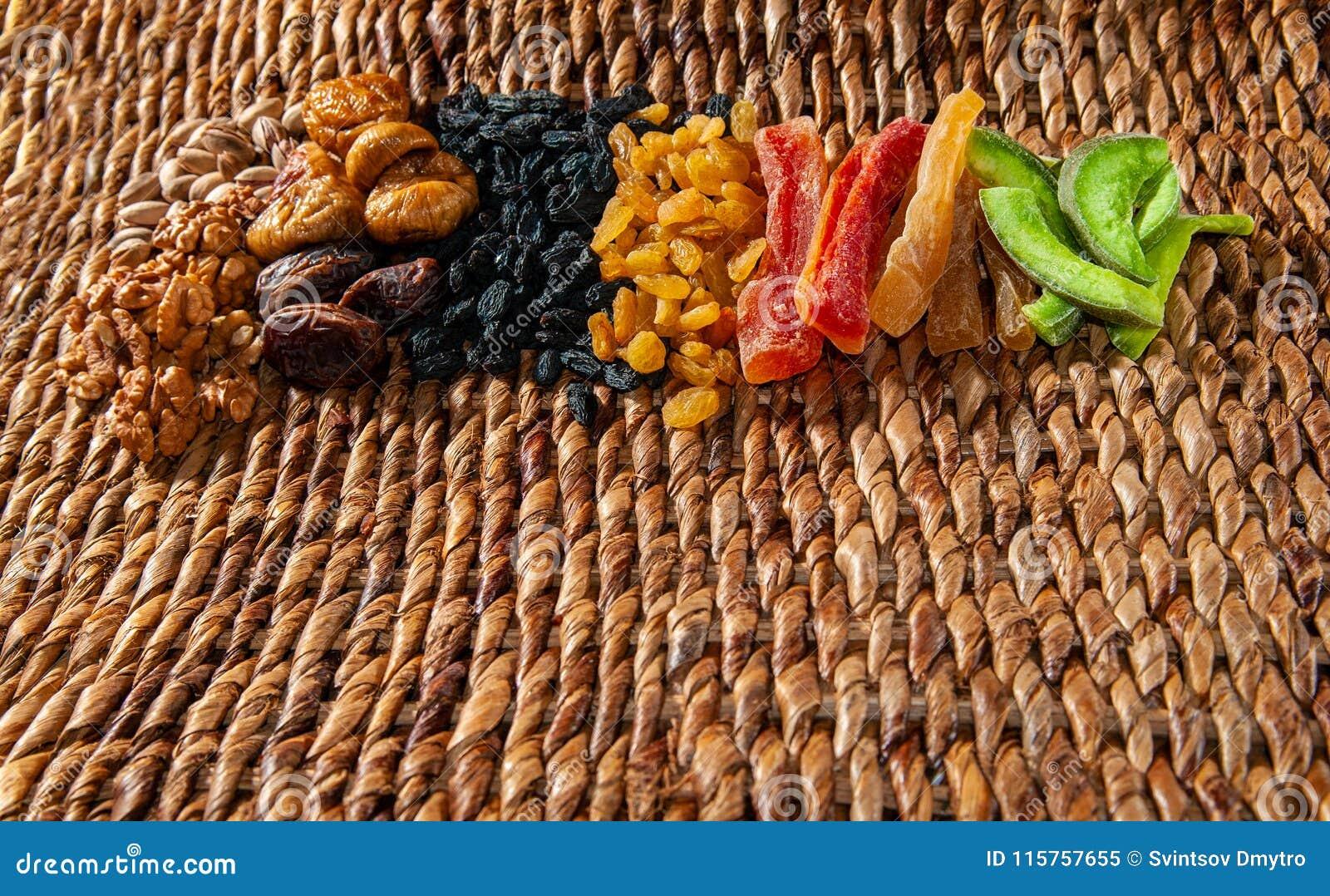 Las frutas secadas de las frutas, nuts y escarchadas extendieron por una superficie de mimbre