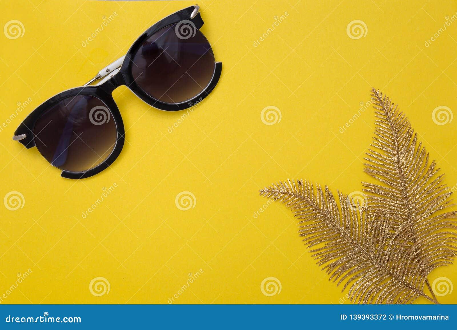 Las gafas de sol de las mujeres y dos hojas del oro de una mentira de la palmera en un fondo amarillo