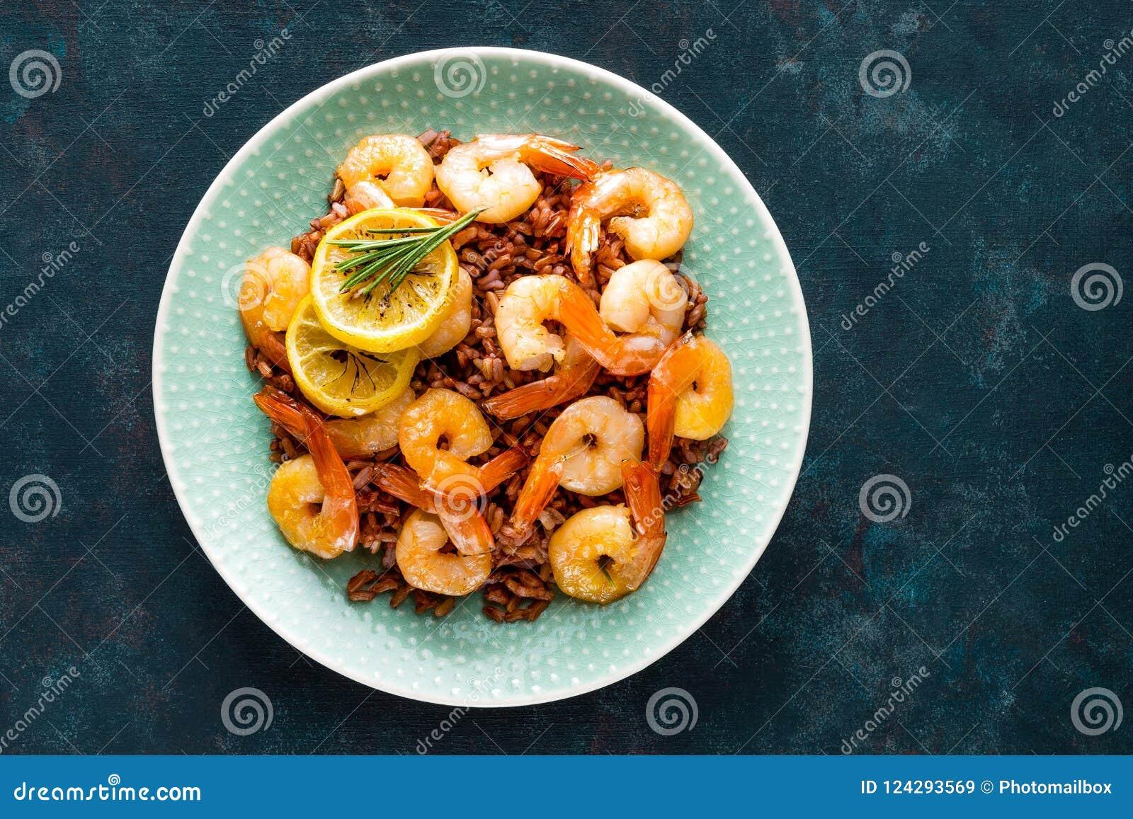 Las gambas asaron en parrilla e hirvieron el arroz moreno en la placa Camarones asados a la parrilla, gambas con arroz Mariscos C