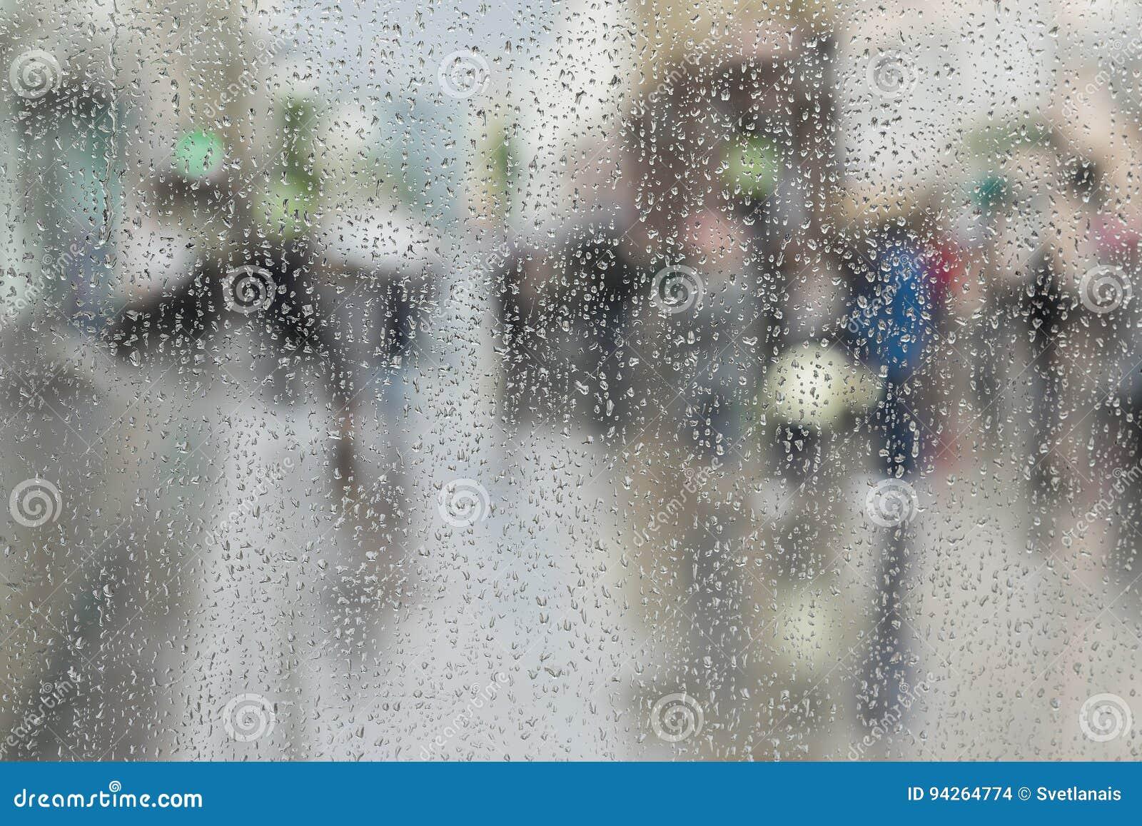 Las gotas de agua en el vidrio de la ventana, gente caminan en el camino en el día lluvioso, fondo borroso del extracto del movim