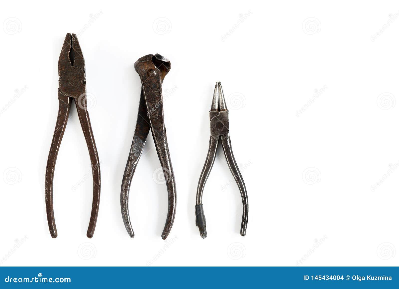 Las herramientas viejas mienten en un fondo aislado blanco Cinceles, cortaalambres, alicates, pinzas y otras herramientas