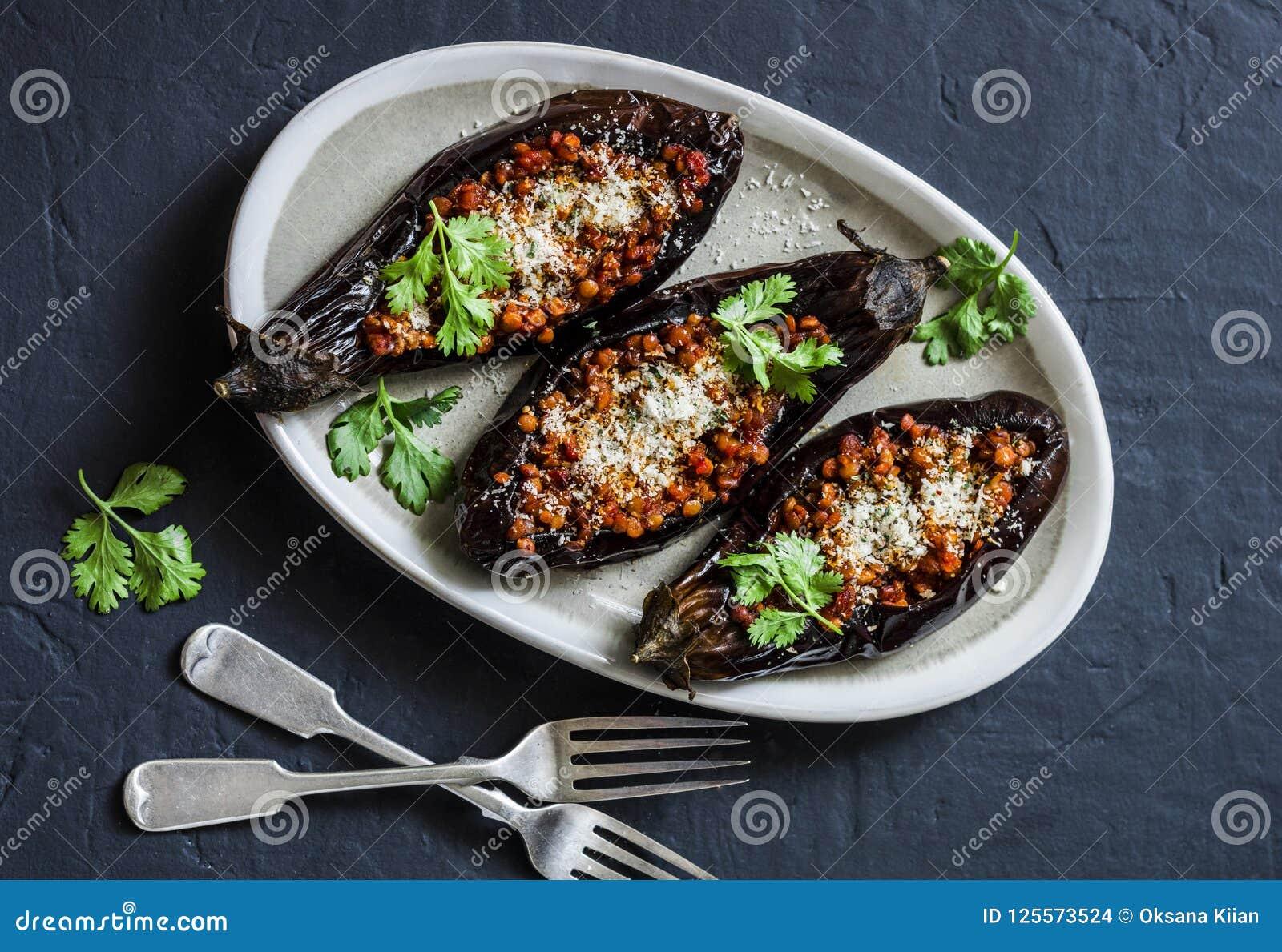 Las lentejas rellenas asaron la berenjena - almuerzo vegetariano sano delicioso, bocado, aperitivo en un fondo oscuro