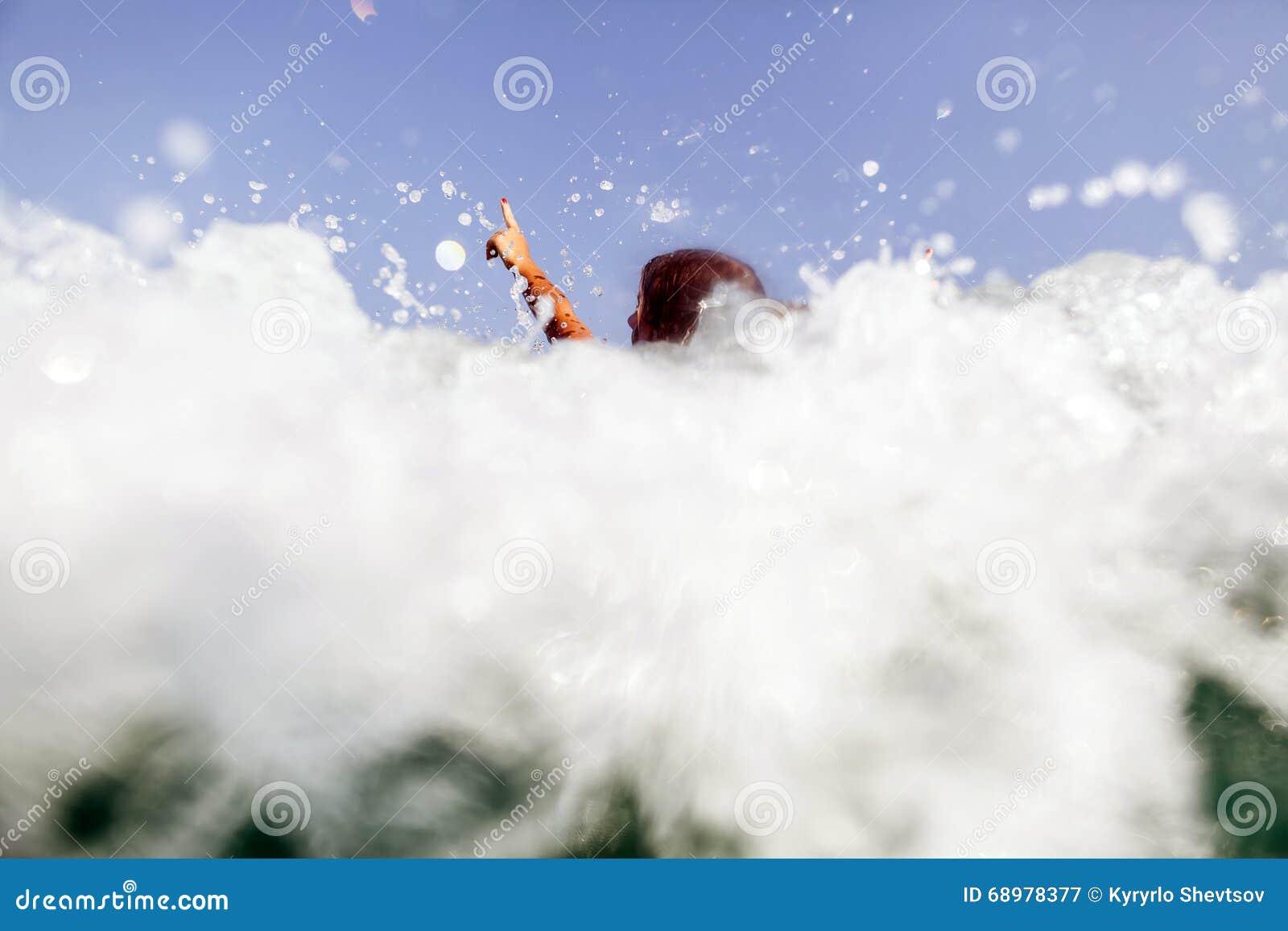 Las manos atractivas de las ondas del mar de la nadada de la muchacha para arriba salpican detrás la visión