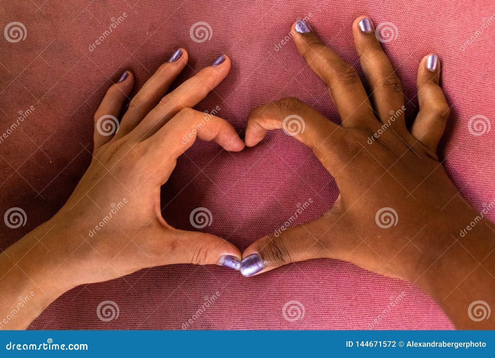 Las manos blancas y negras de novias forman un corazón de fingeres contra racismo