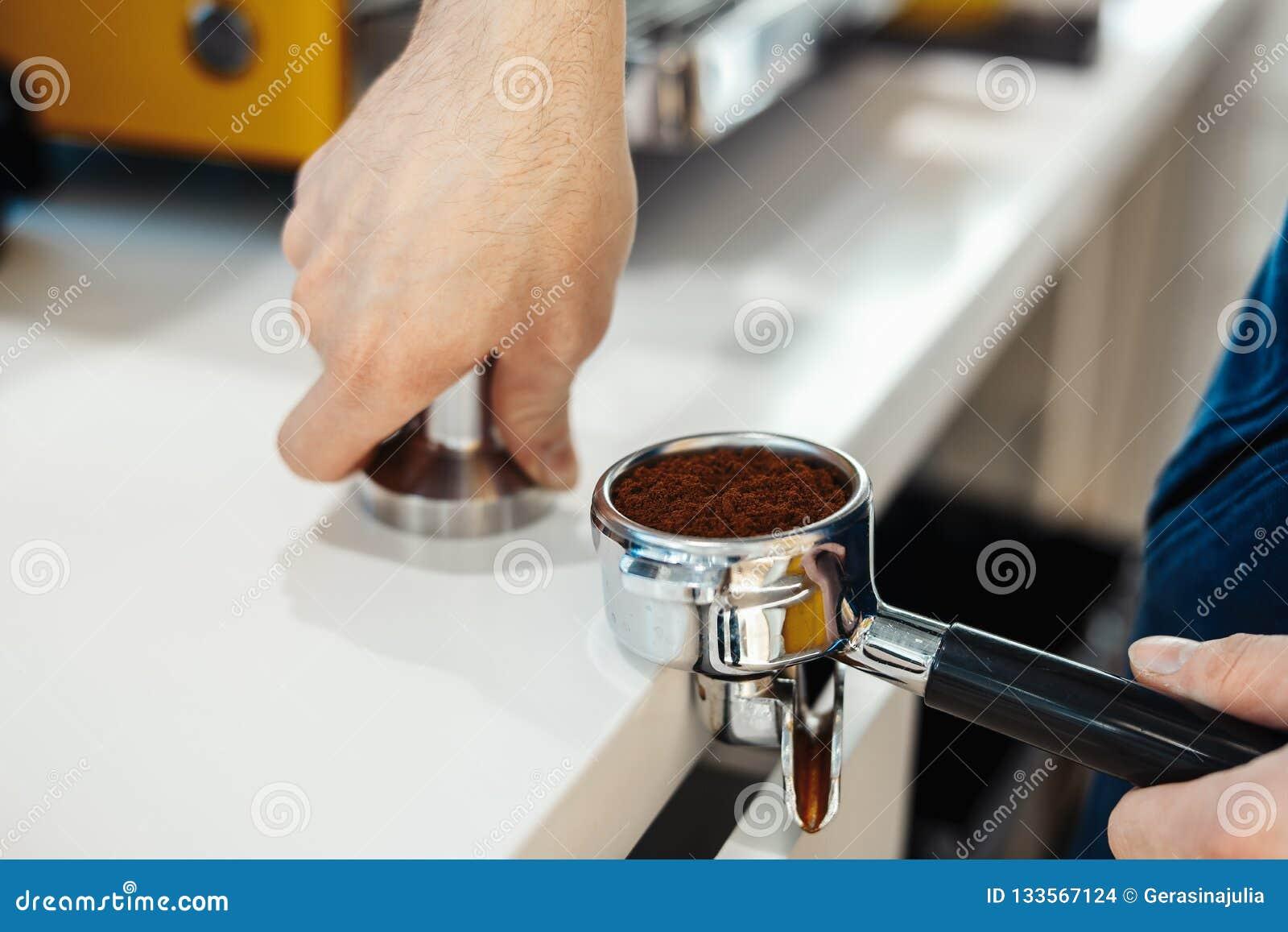 Las manos de Barista que sostienen el portafilter y el café tratan de forzar haciendo un café del café express
