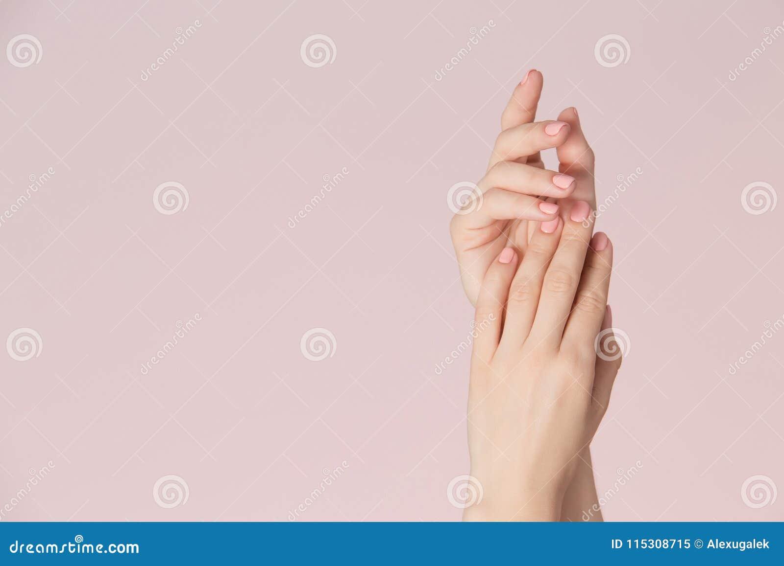 Las manos de la mujer con la piel limpia y los clavos con rosa pulen la manicura en fondo rosado Cuidado de los clavos y tema de