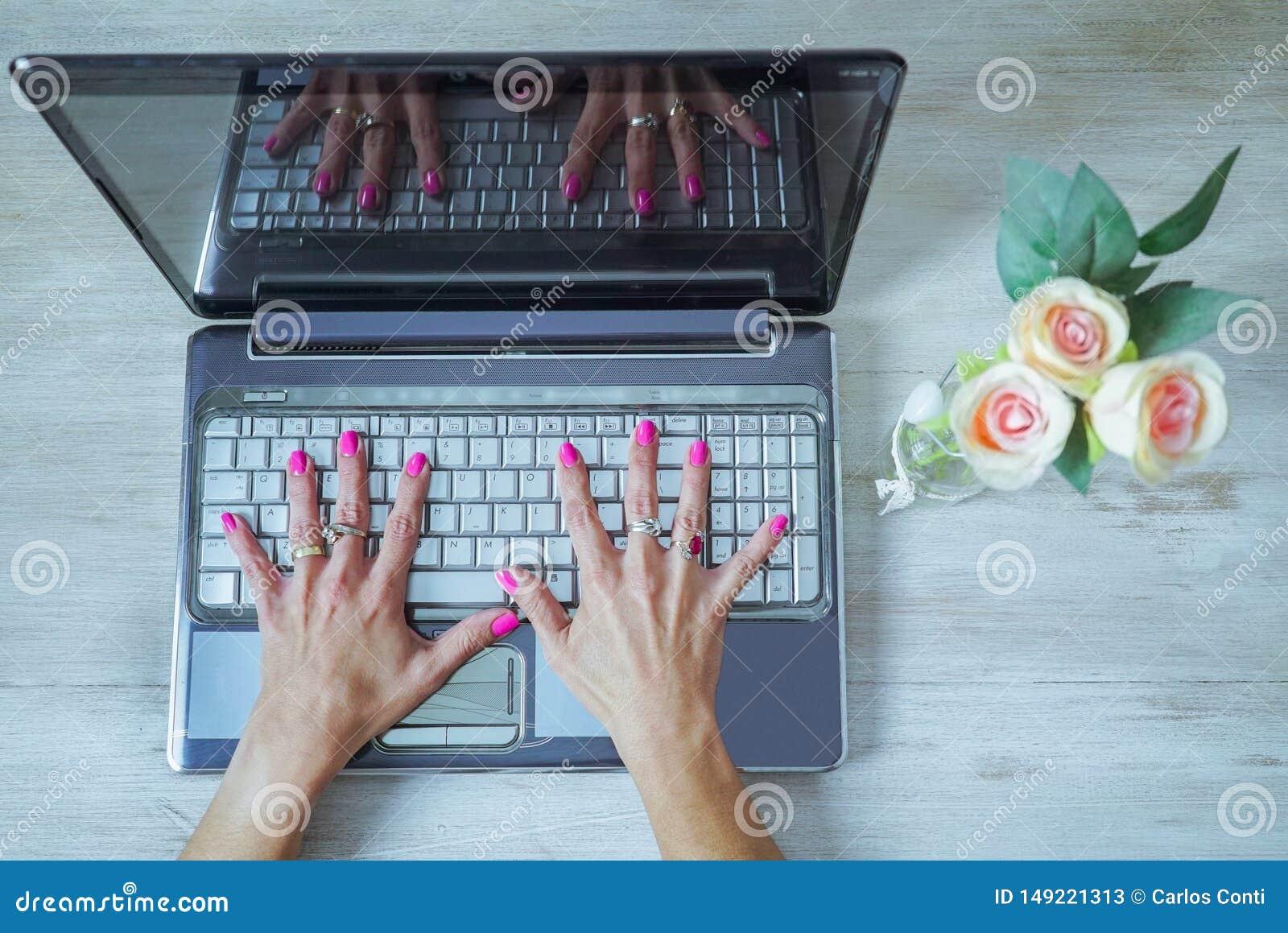 Las manos de la mujer hermosa con los clavos pintados abiertos en un teclado de ordenador