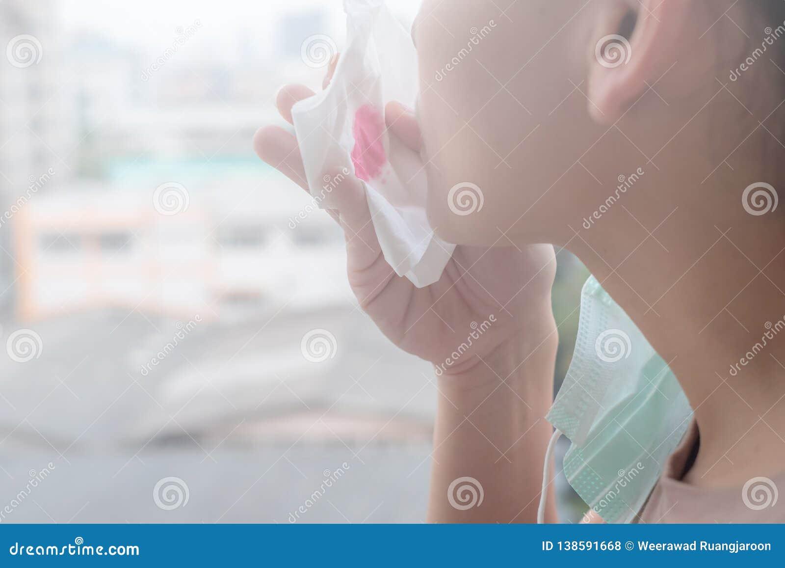 Las manos de la mujer o las manos femeninas que sostienen una máscara protectora y una servilleta con sangre debido a la contamin