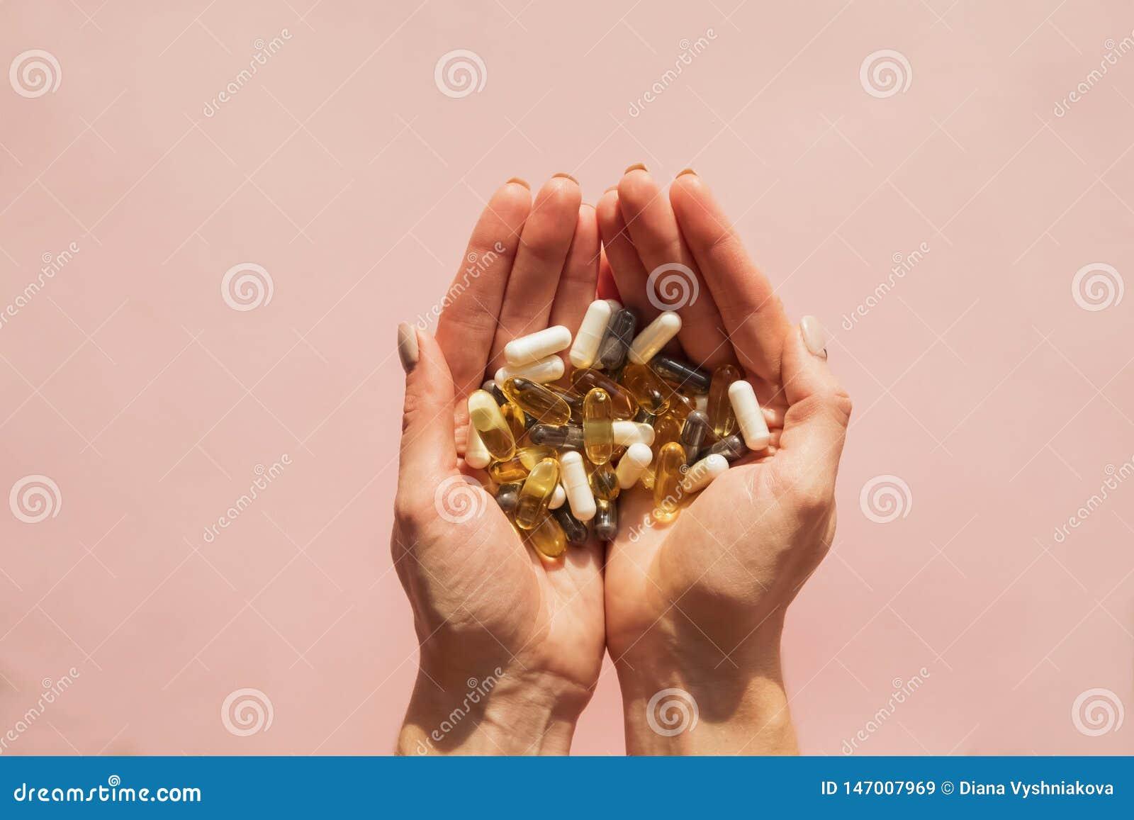 Las manos de la mujer que llevan a cabo muchas diversas píldoras o suplementos dietéticos