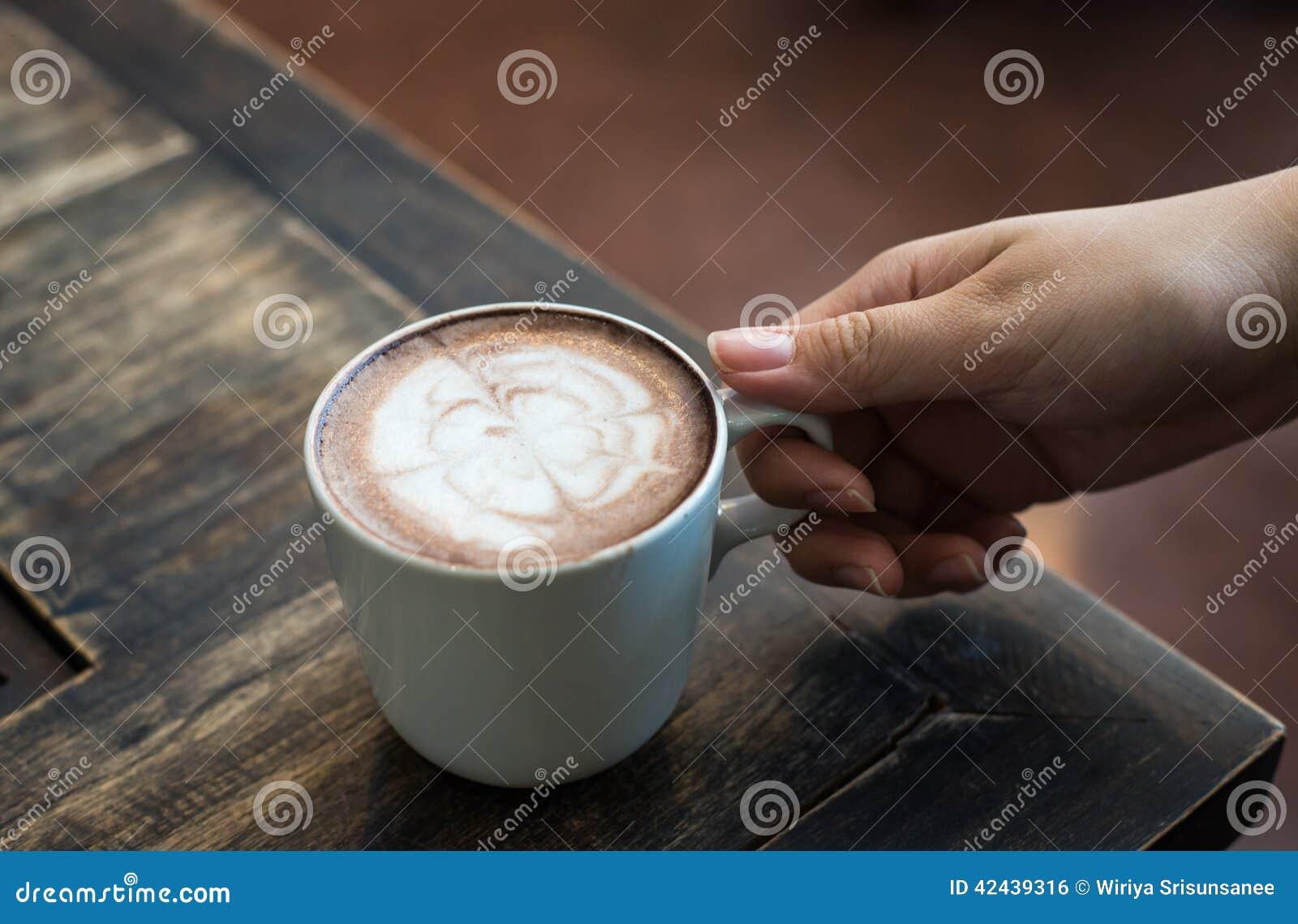 Las manos de la mujer que sostienen la taza de café