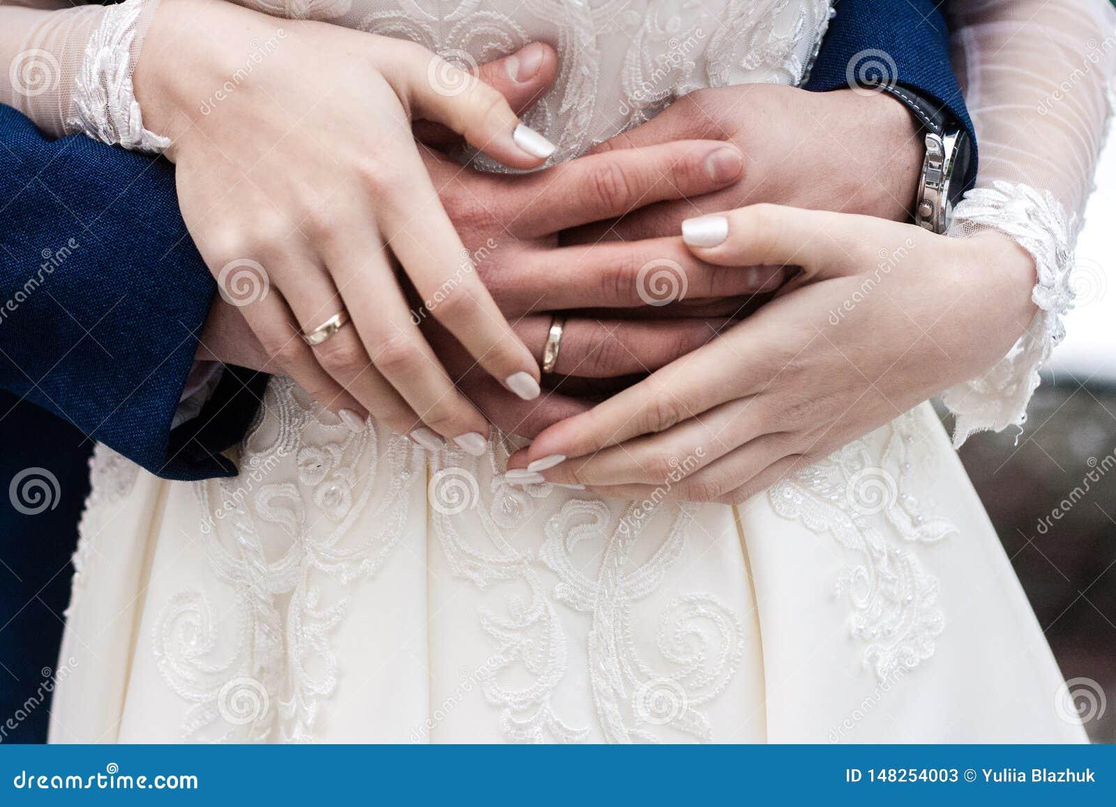 Las manos de la novia y del novio con los anillos se cierran para arriba
