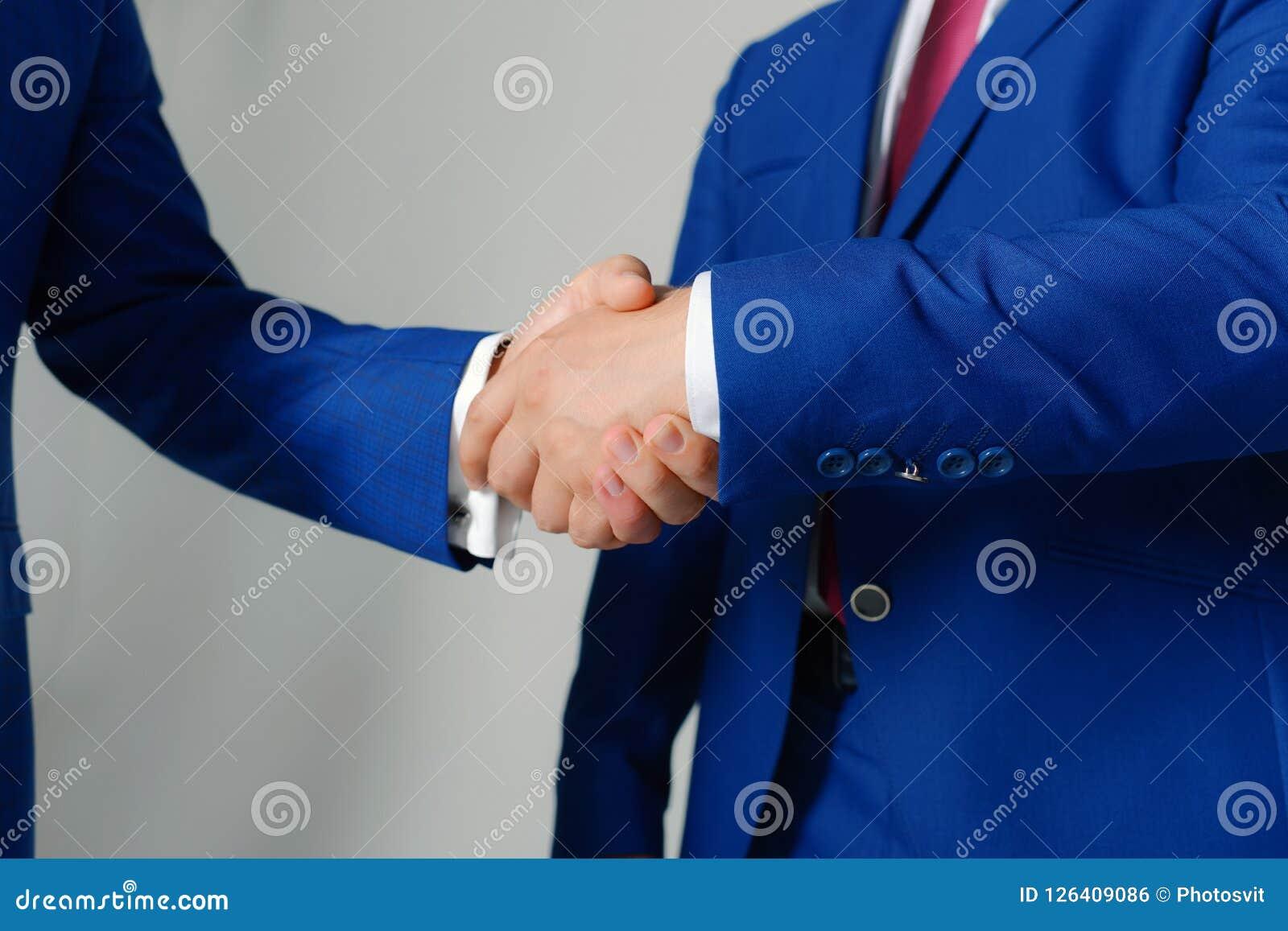 Las manos de los hombres de negocios en trajes formales se saludan Líderes de la compañía