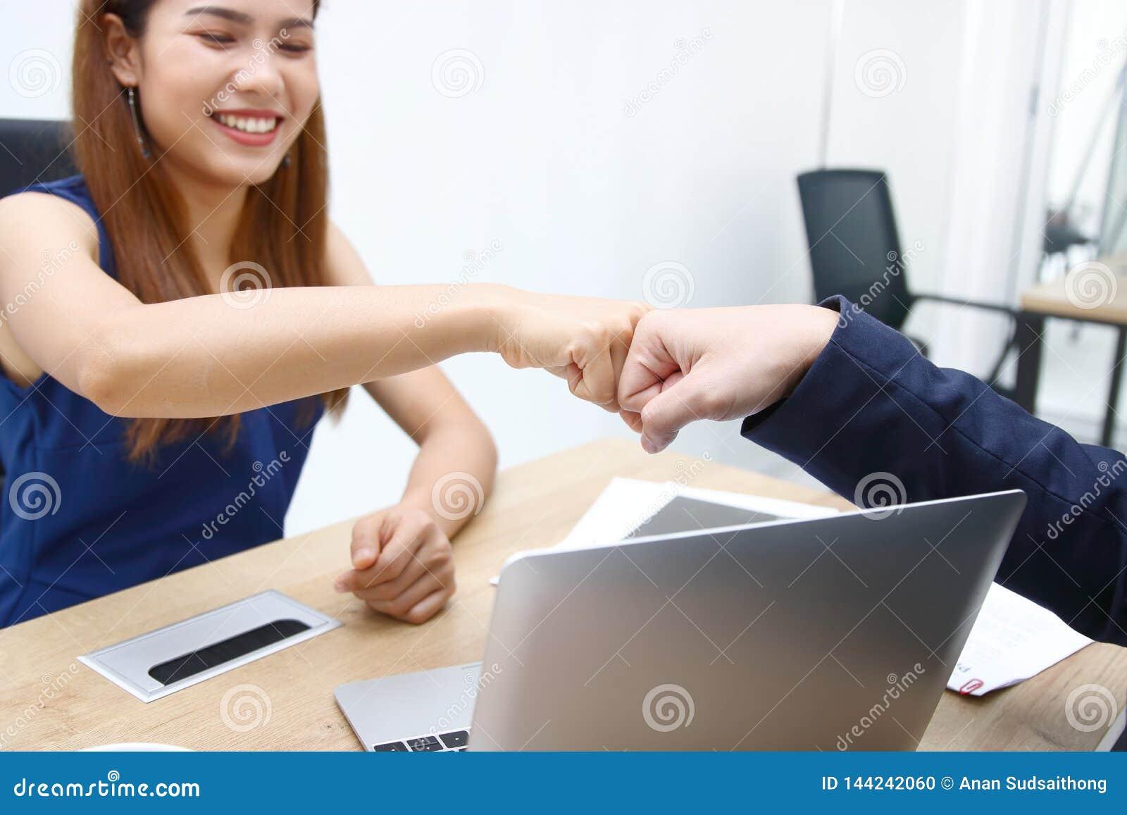 Las manos de los hombres de negocios jovenes que dan el pu?o topan juntas al tratamiento completo de saludo en oficina Concepto d
