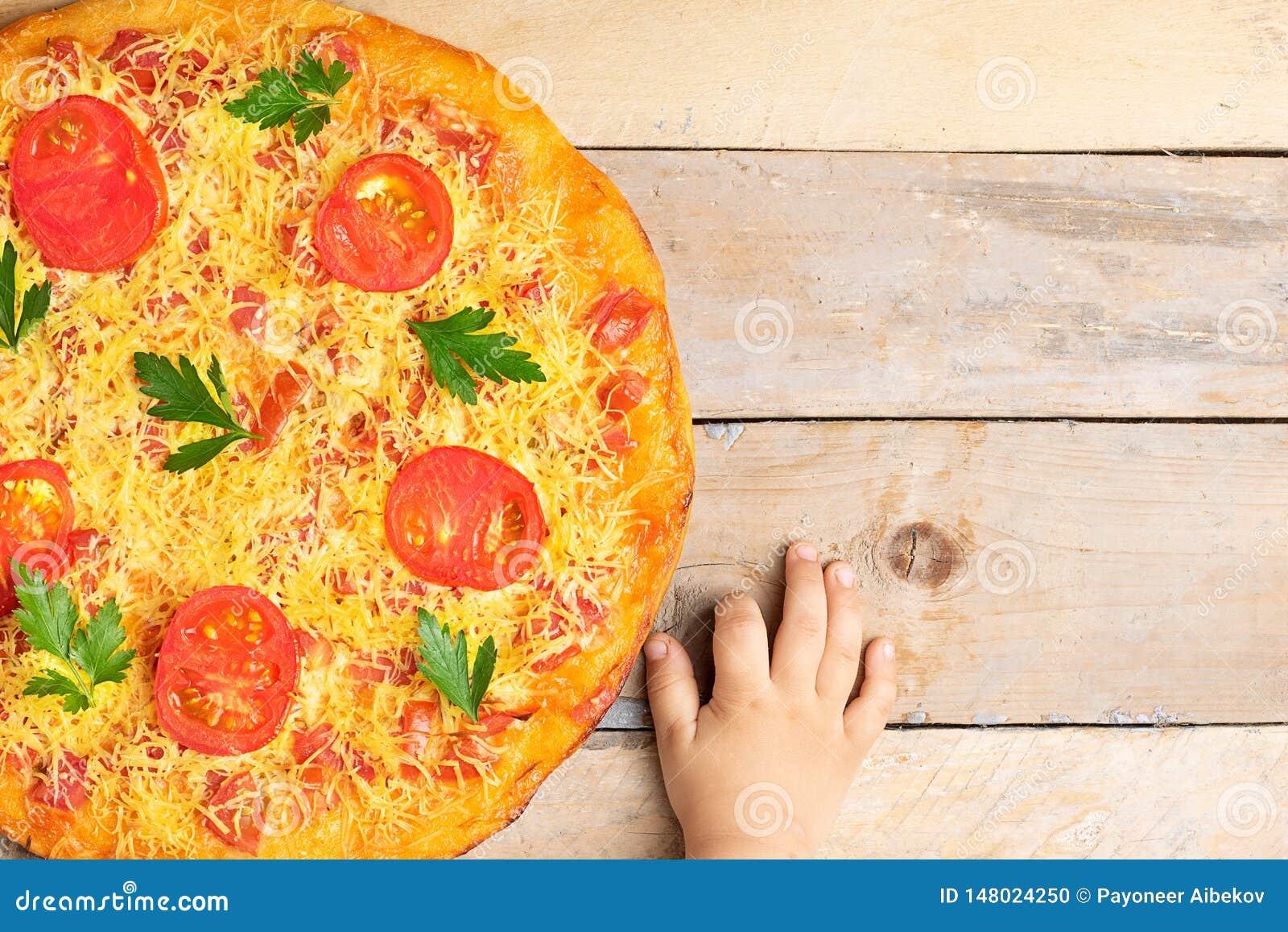 Las manos de los niños sostienen la pizza de queso con los tomates y la albahaca, comida en la tabla rústica de madera, visión su