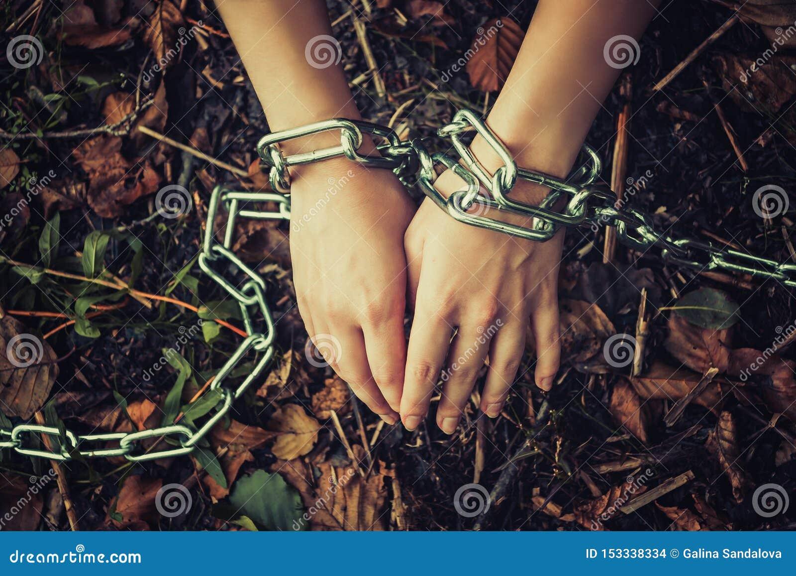 Las manos de las mujeres encadenaron en un bosque oscuro - el concepto de violencia, rehén, esclavitud