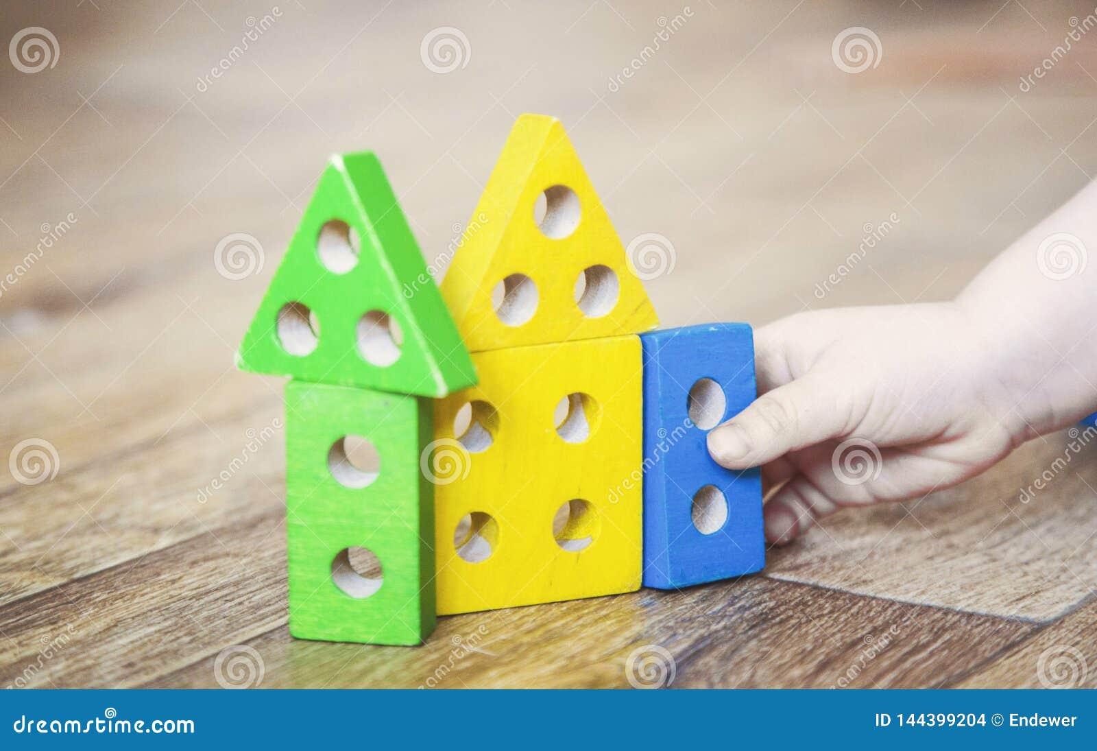 Las manos de una muchacha del ni?o que juega los juguetes E