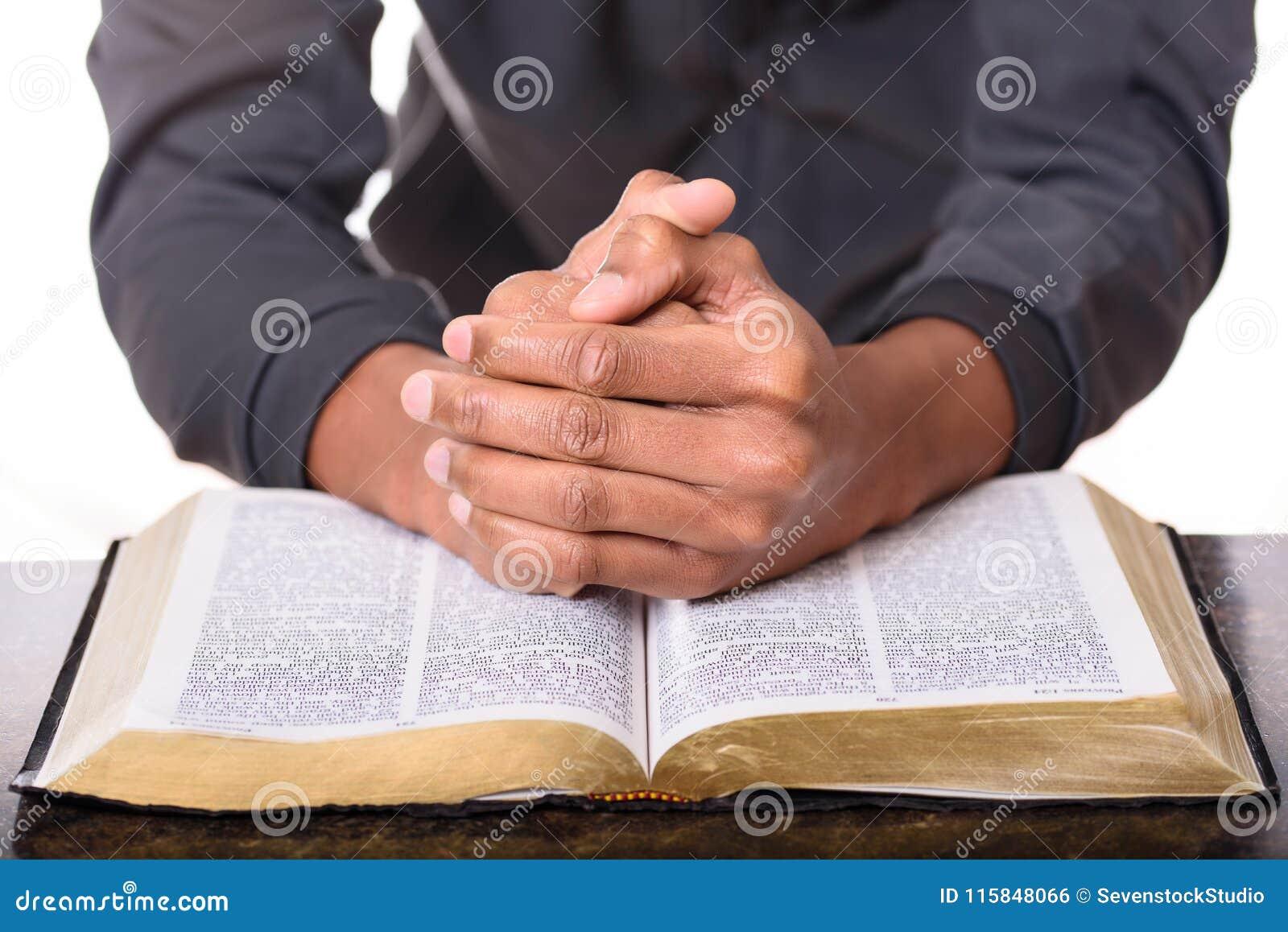 Las manos de una rogación doblada del hombre joven sobre una biblia, entregan la biblia suave del foco
