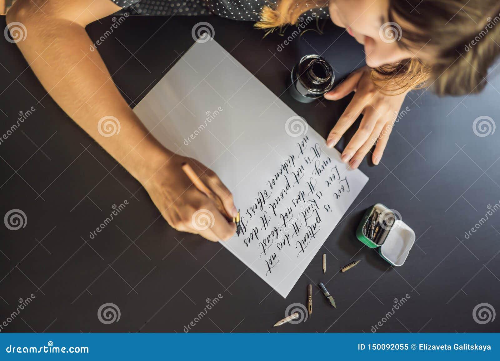 Las manos del cal?grafo escriben frase en el Libro Blanco Frase de la biblia sobre el amor que inscribe letras adornadas ornament