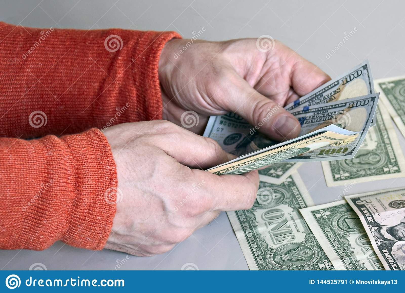 Las manos del hombre caucásico que cuentan billetes de banco del dólar
