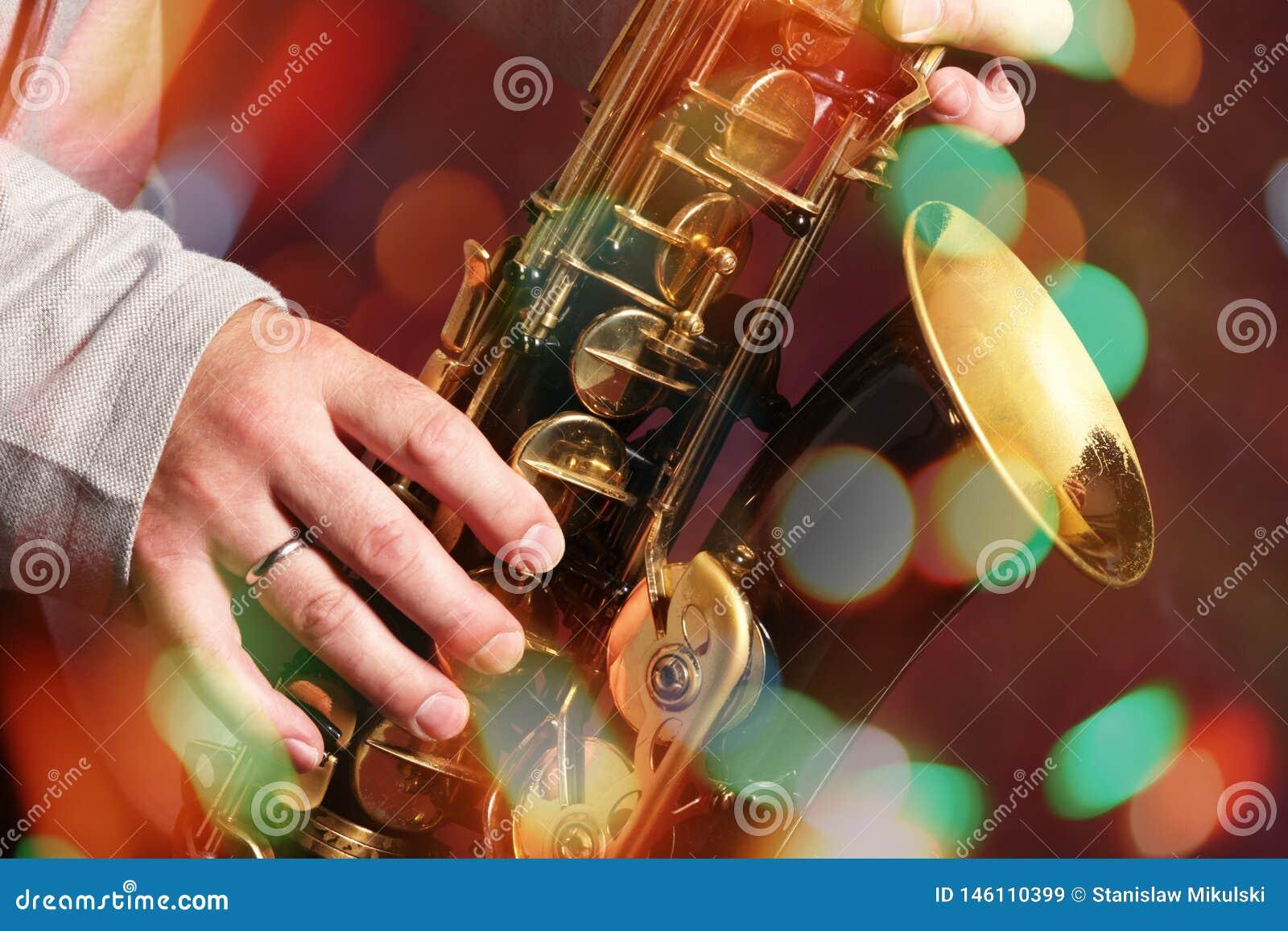 Las manos del hombre con el saxofón en luces del bokeh
