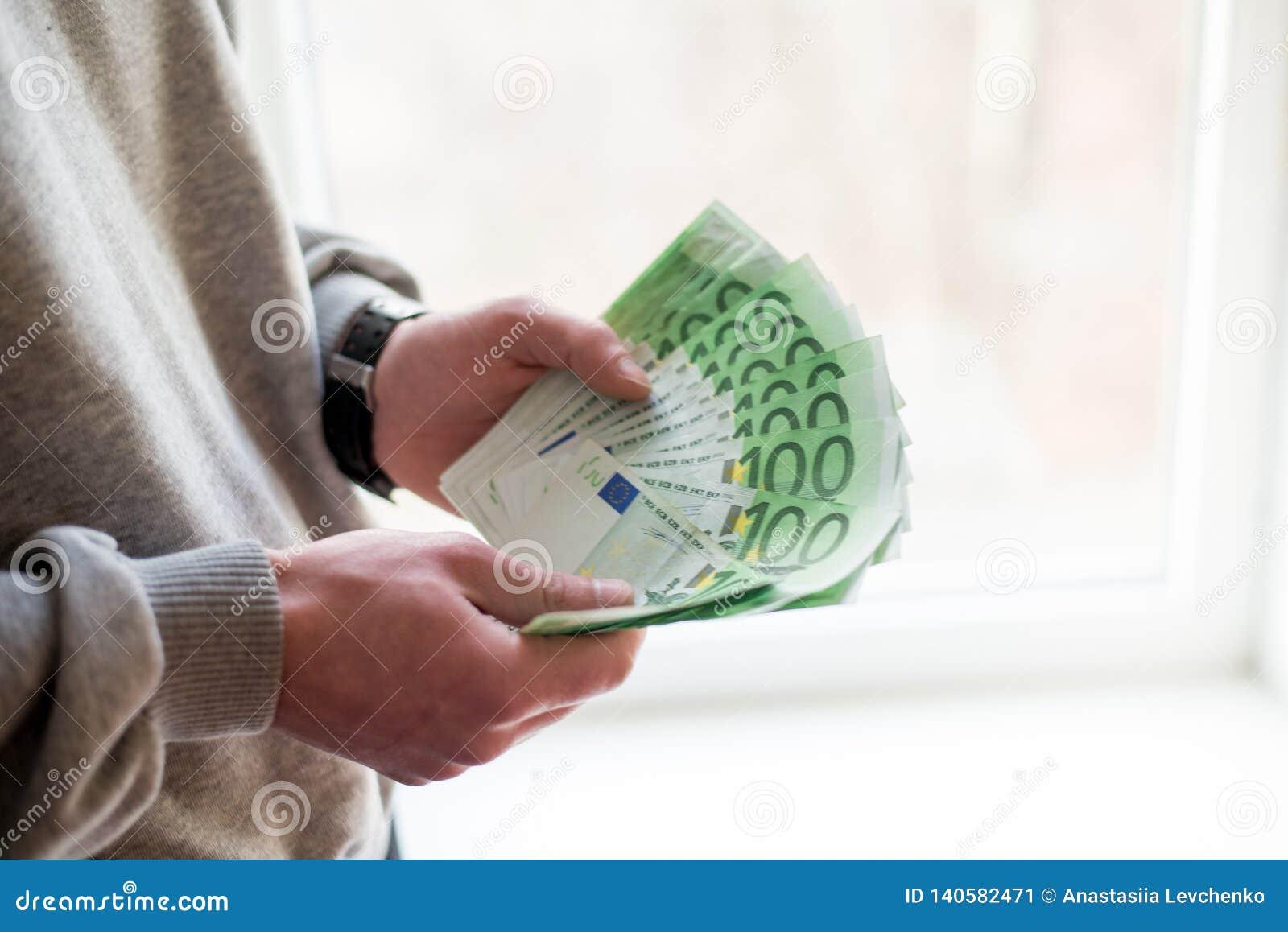 Las manos del hombre con euro en el fondo blanco Concepto financiero del negocio