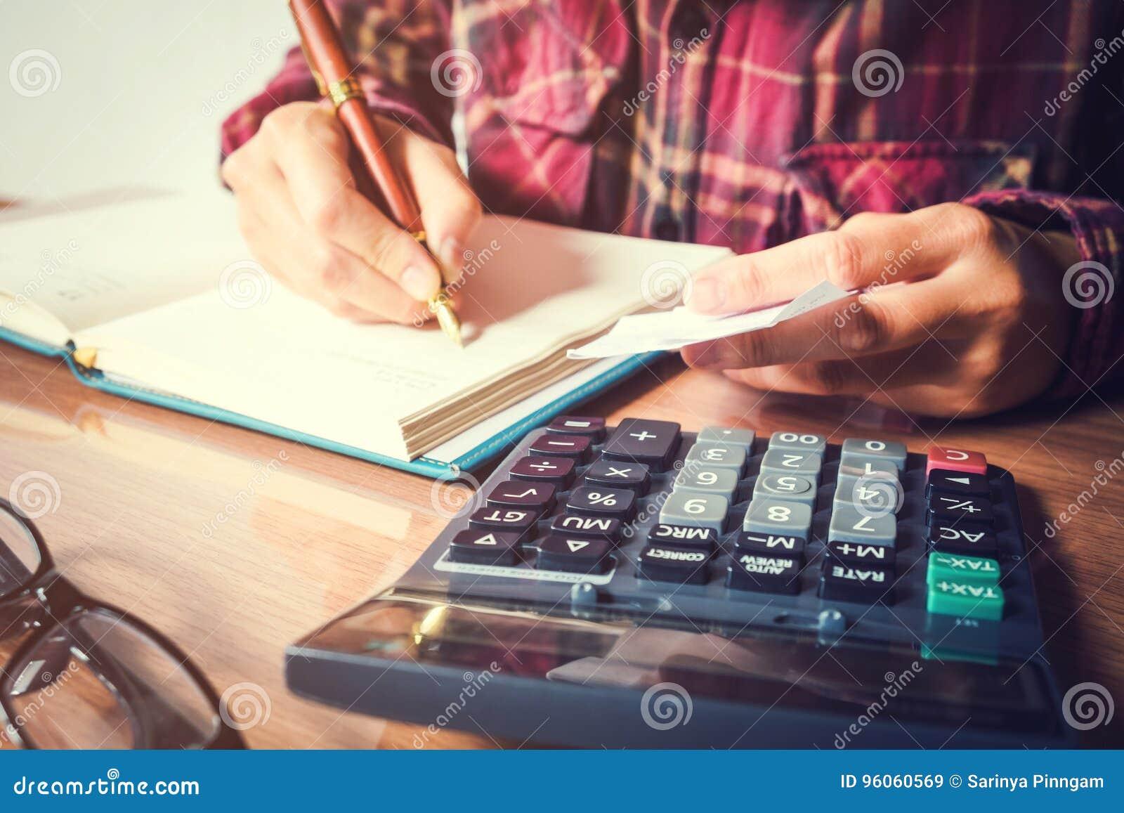 Las manos del hombre de negocios con la calculadora que cuenta haciendo notas en el hom