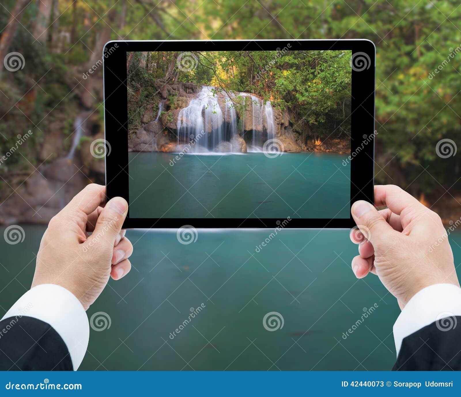 Las manos del hombre de negocios hacen tabletas tomar a cascada de las imágenes el bosque profundo