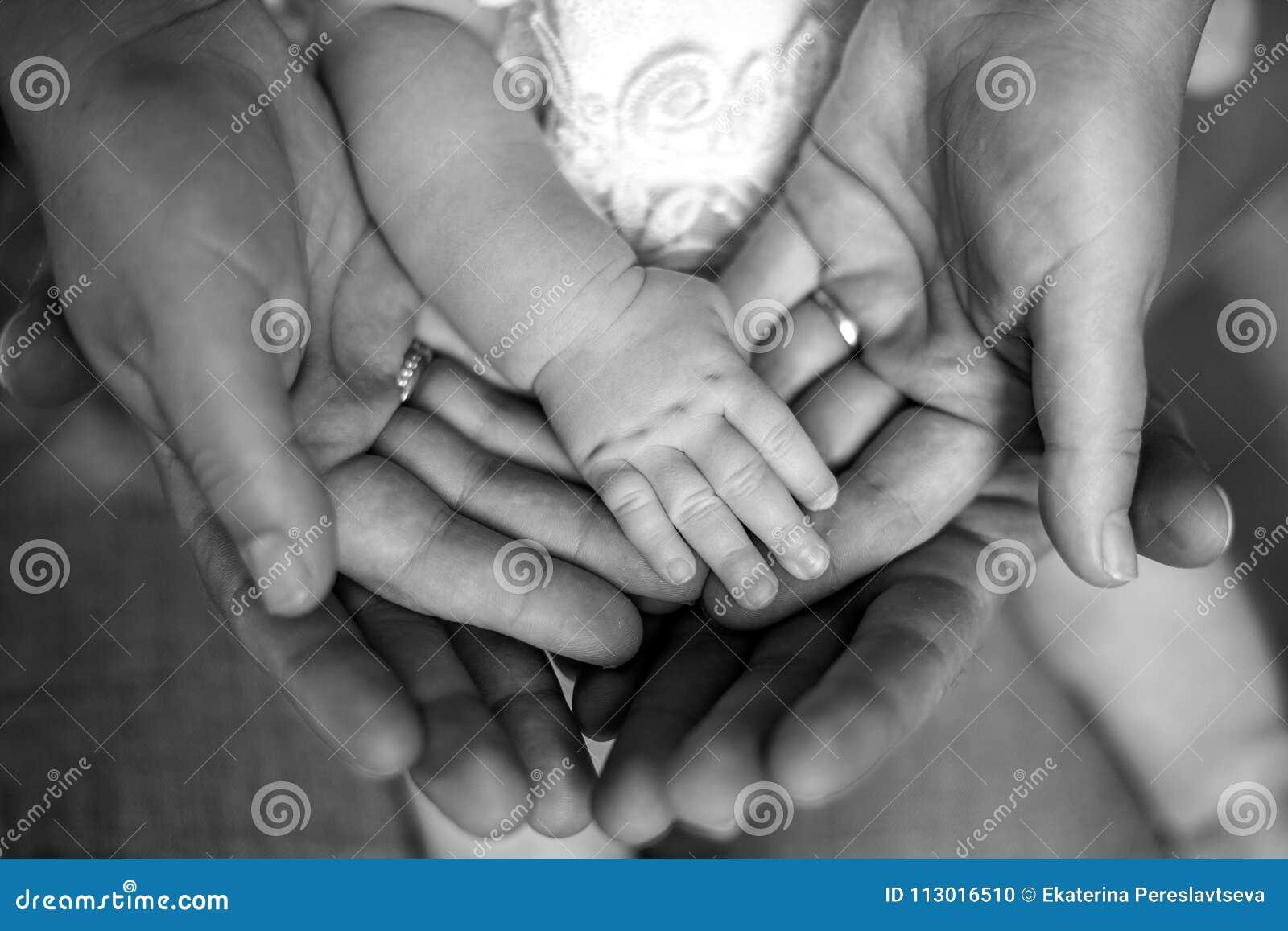 Las manos del padre, madre, guardan al pequeño bebé de los pies Familia feliz amistosa, foto blanco y negro de las familias de la