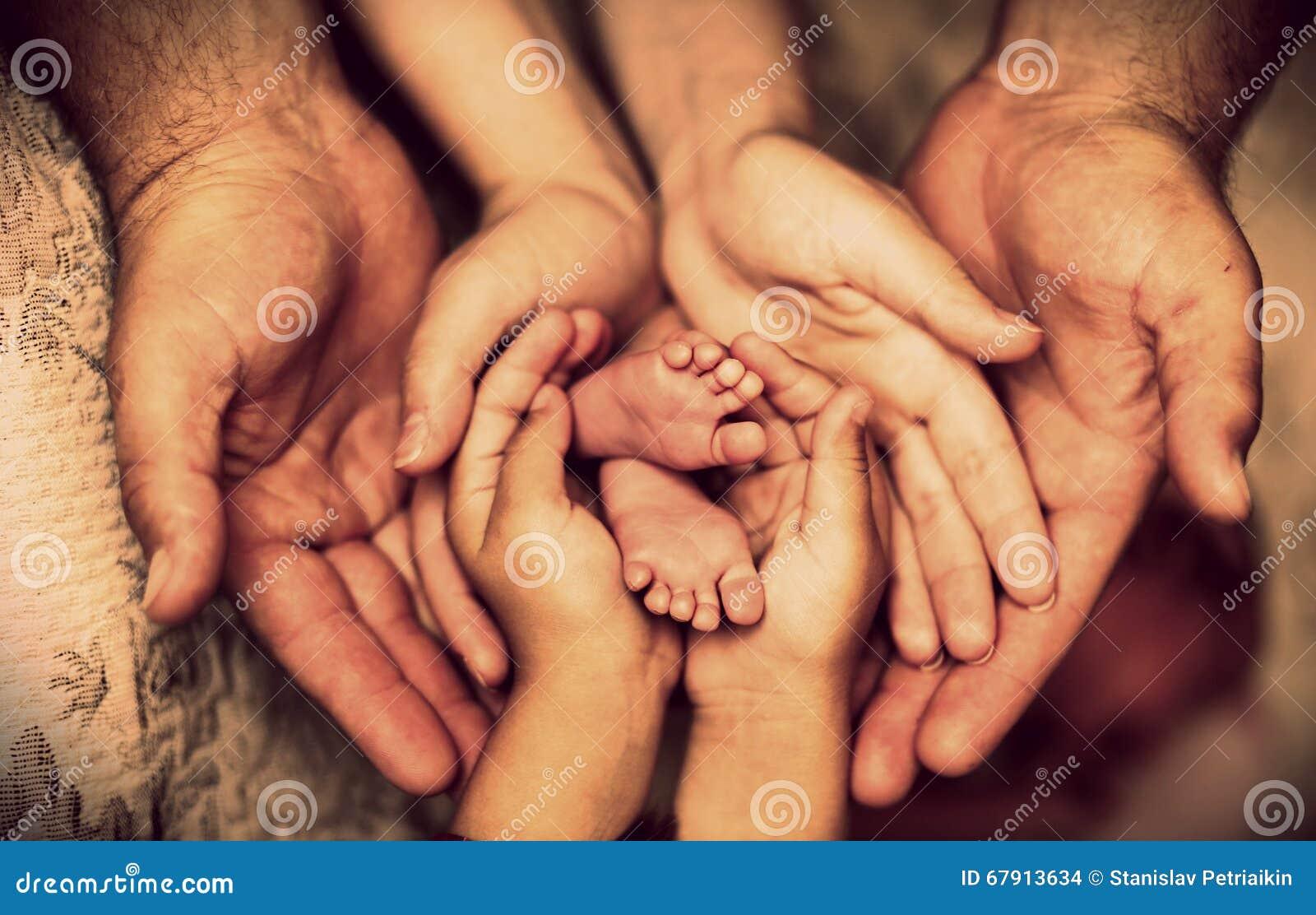 Las manos del padre, madre, hija guardan al pequeño bebé de los pies Familia feliz amistosa