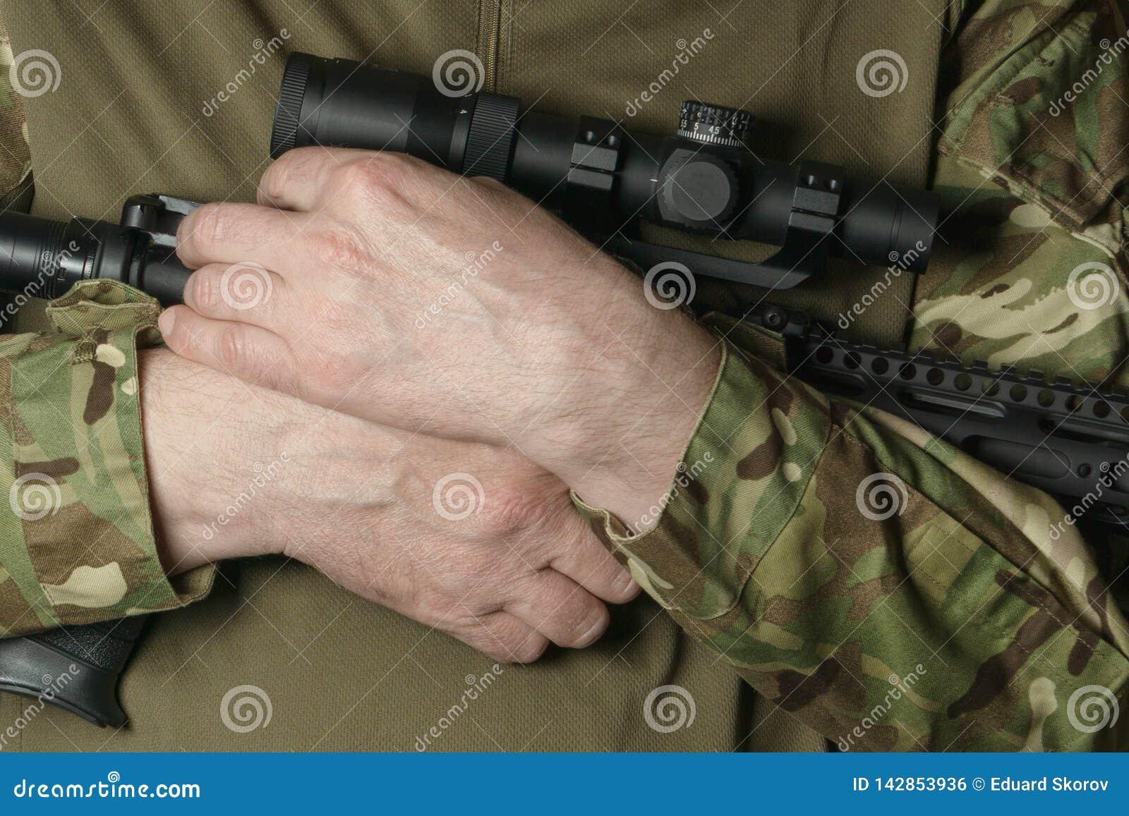Las manos del soldado en camuflaje sostener un rifle