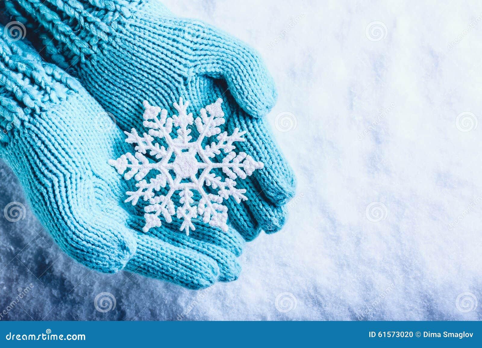 Las manos femeninas en trullo ligero hicieron punto las manoplas con el copo de nieve maravilloso chispeante en un fondo blanco d